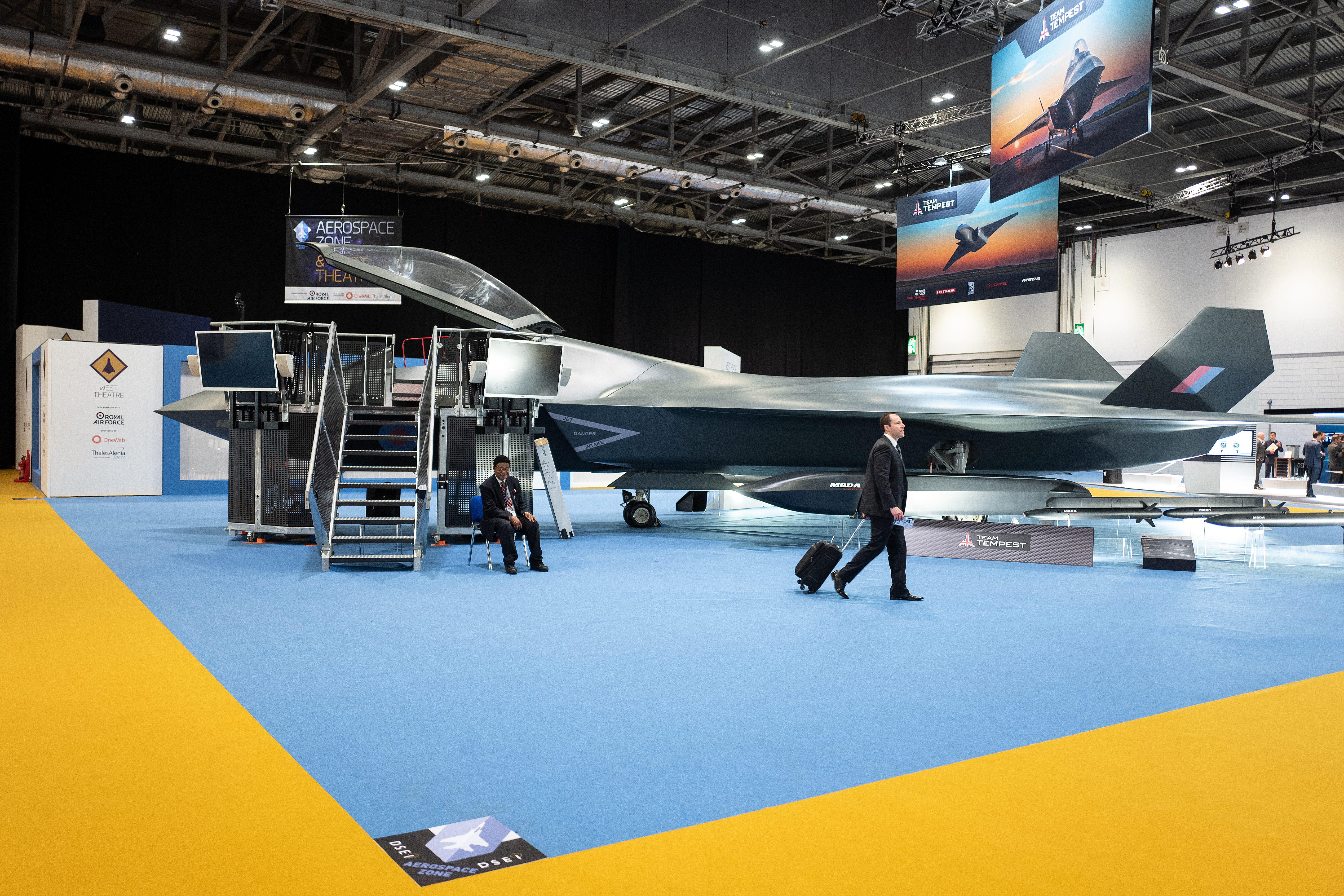 At the DSEI arms fair, a delegate walks past a model of the BAE Systems Tempest fighter jet. (Leon Neal/Getty Images)