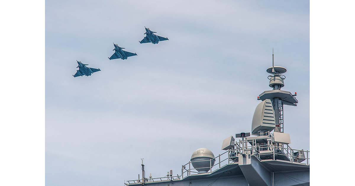 A flight of three French Rafale Marine fighter aircraft pass the island of the aircraft carrier George H.W. Buch as they head into