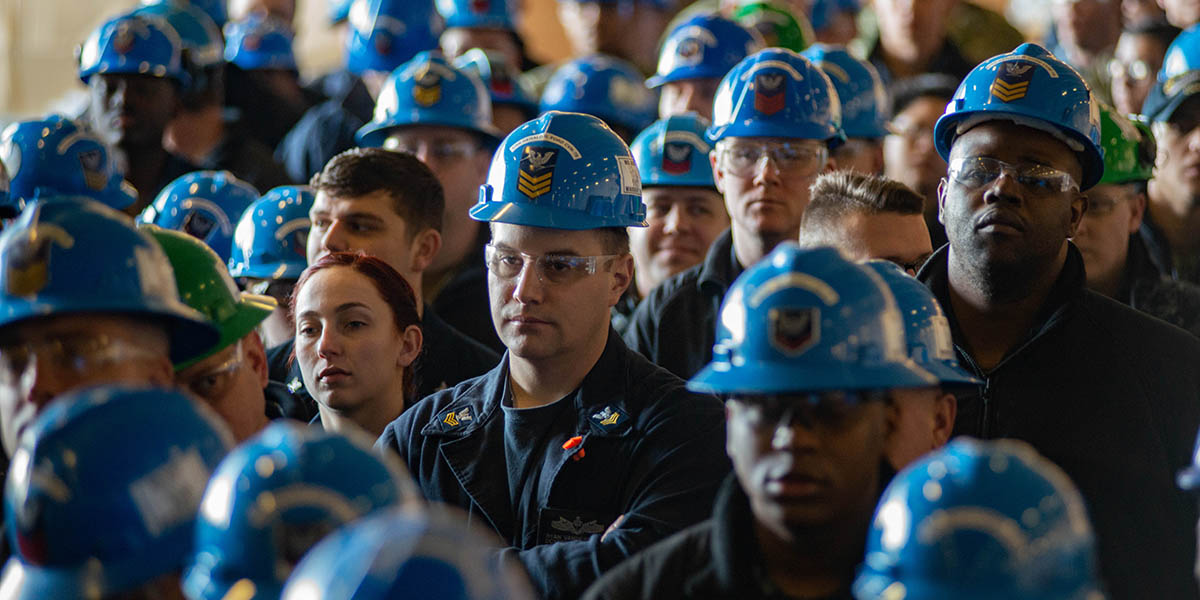 Crew members from the aircraft carrier Gerald R. Ford listen to Chief of Naval Operations Adm. John Richardson on the ship's hanger bay (Mark D. Faram/staff)