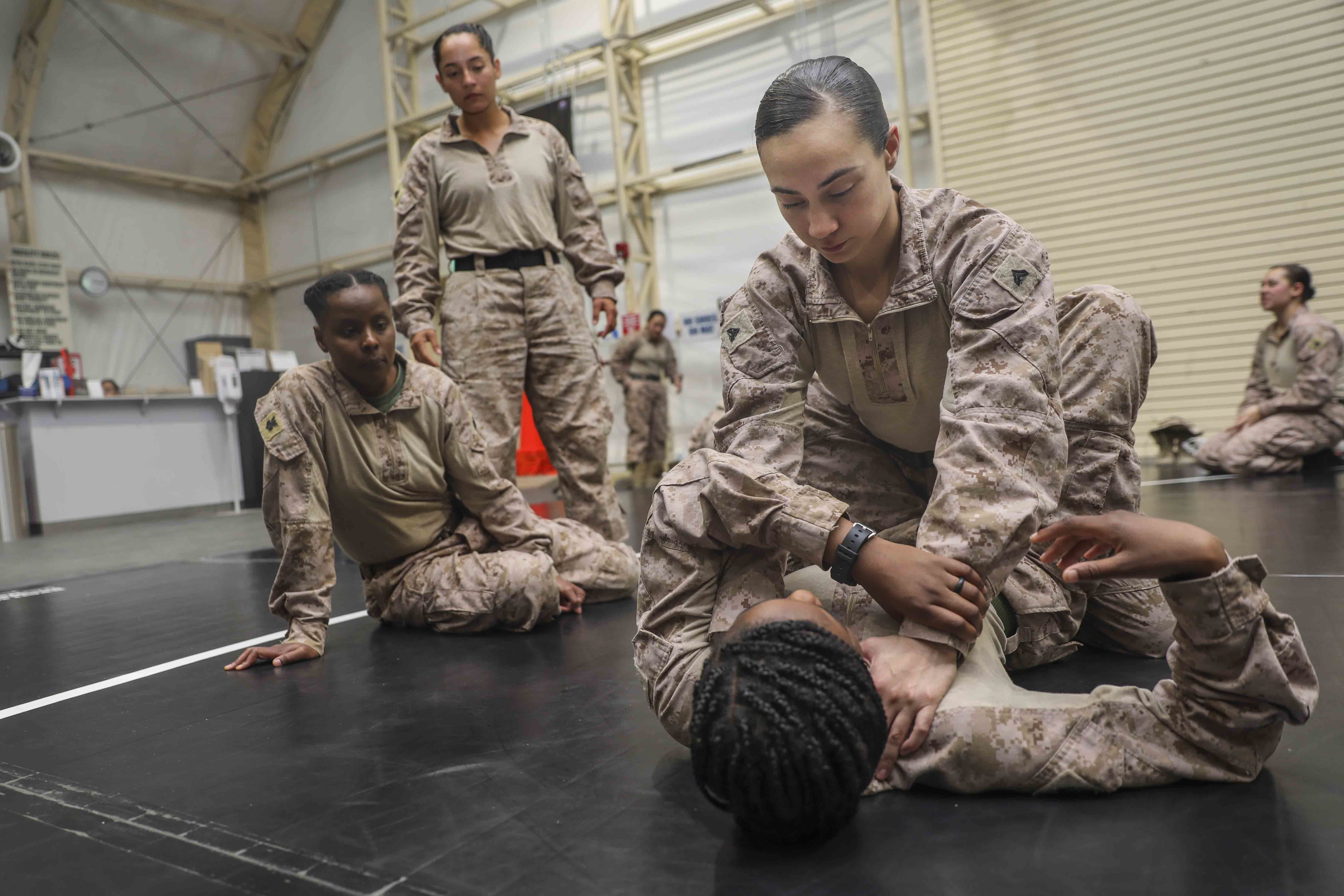 Cpl. Erin Thomas, top, a law enforcement Marine, and Cpl. Damionia Lott, an administrative specialist, practice Marine Corps Martial Arts Program techniques as a part of training at Camp Buehring in Kuwait on April 10, 2019. (Cpl. Tawanya Norwood/Marine Corps)