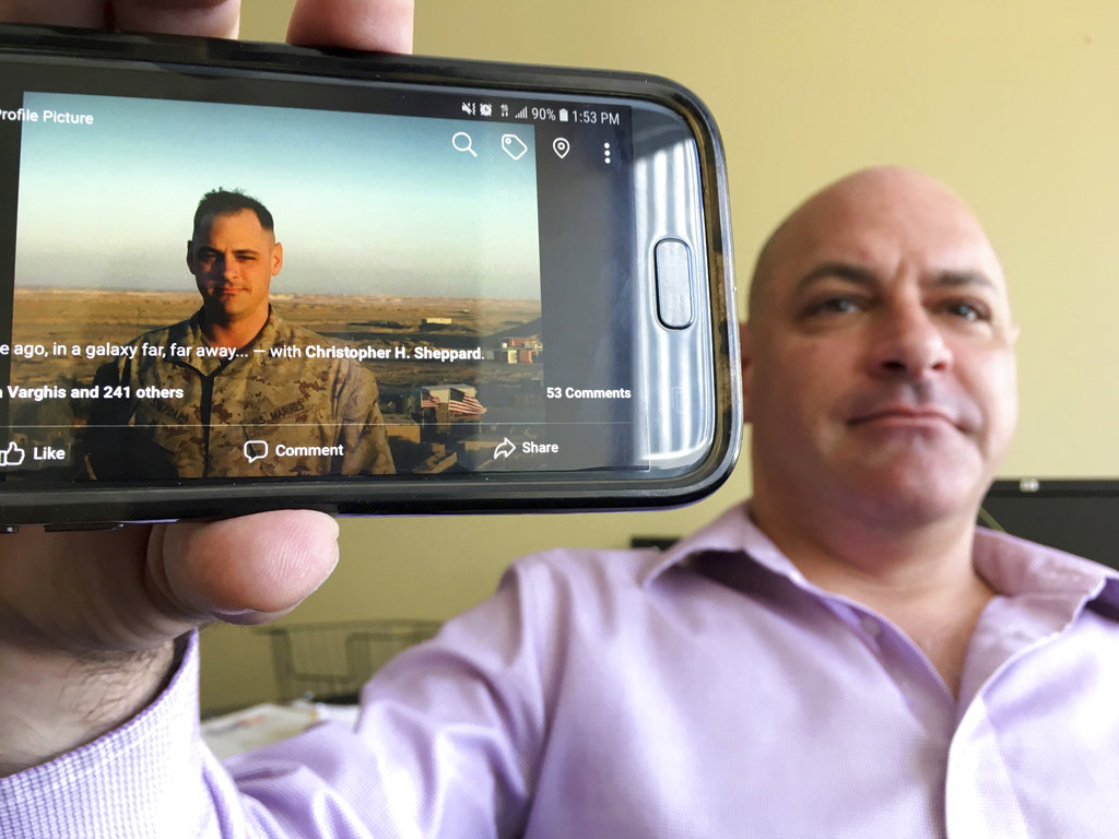 In this photograph taken July 17, 2018, Marine Corps veteran Chris Sheppard poses with a picture of himself taken during his service in Iraq in October 2004, at his office in Seattle. (Manuel Valdes/AP)