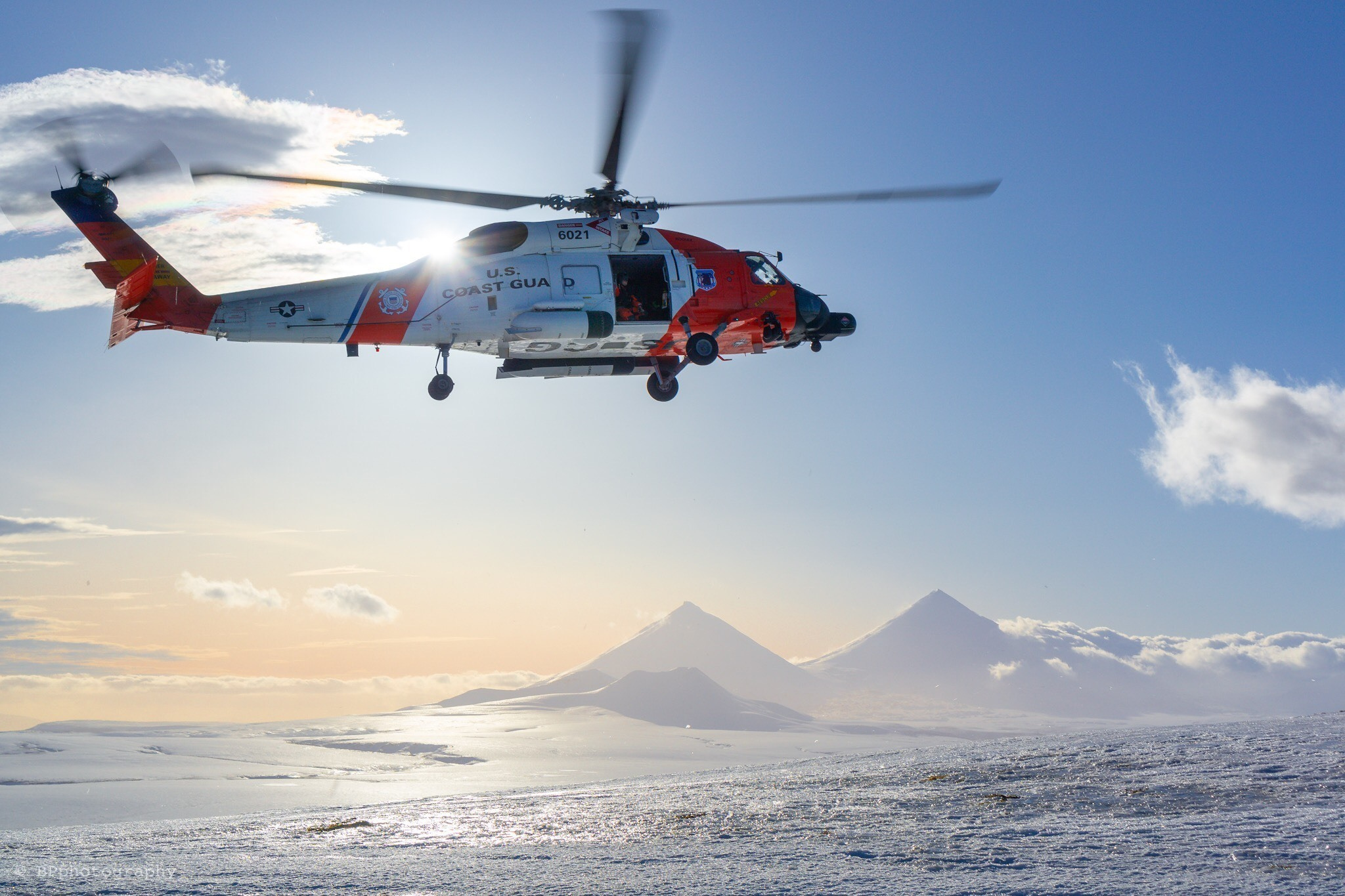 A U.S. Coast Guard MH-60 Jayhawk helicopter assigned to Air Station Kodiak flies over an active volcano near Cold Bay, Alaska, Feb. 7, 2019. (Petty Officer 1st Class Bradley Pigage/Coast Guard)