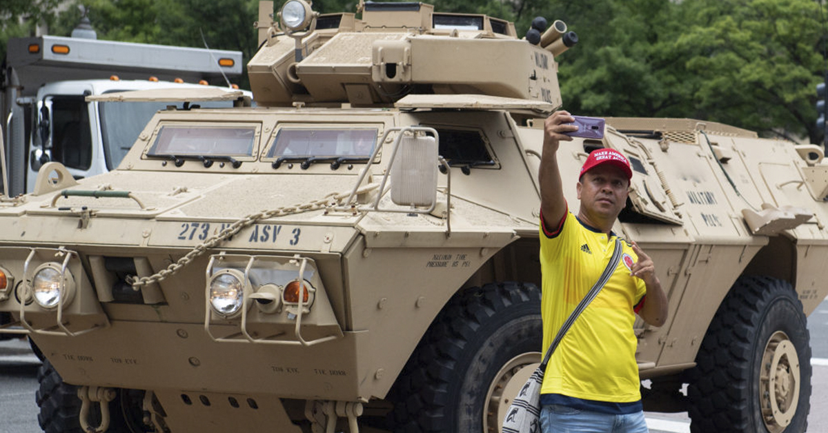 A man takes a photo near an armored military vehicle during the Fourth of July parade in Washington, DC, July 4, 2019. Tanks in the heart of Washington, fighter jets screaming overhead, and a speech from the Lincoln Memorial: President Donald Trump has promised the