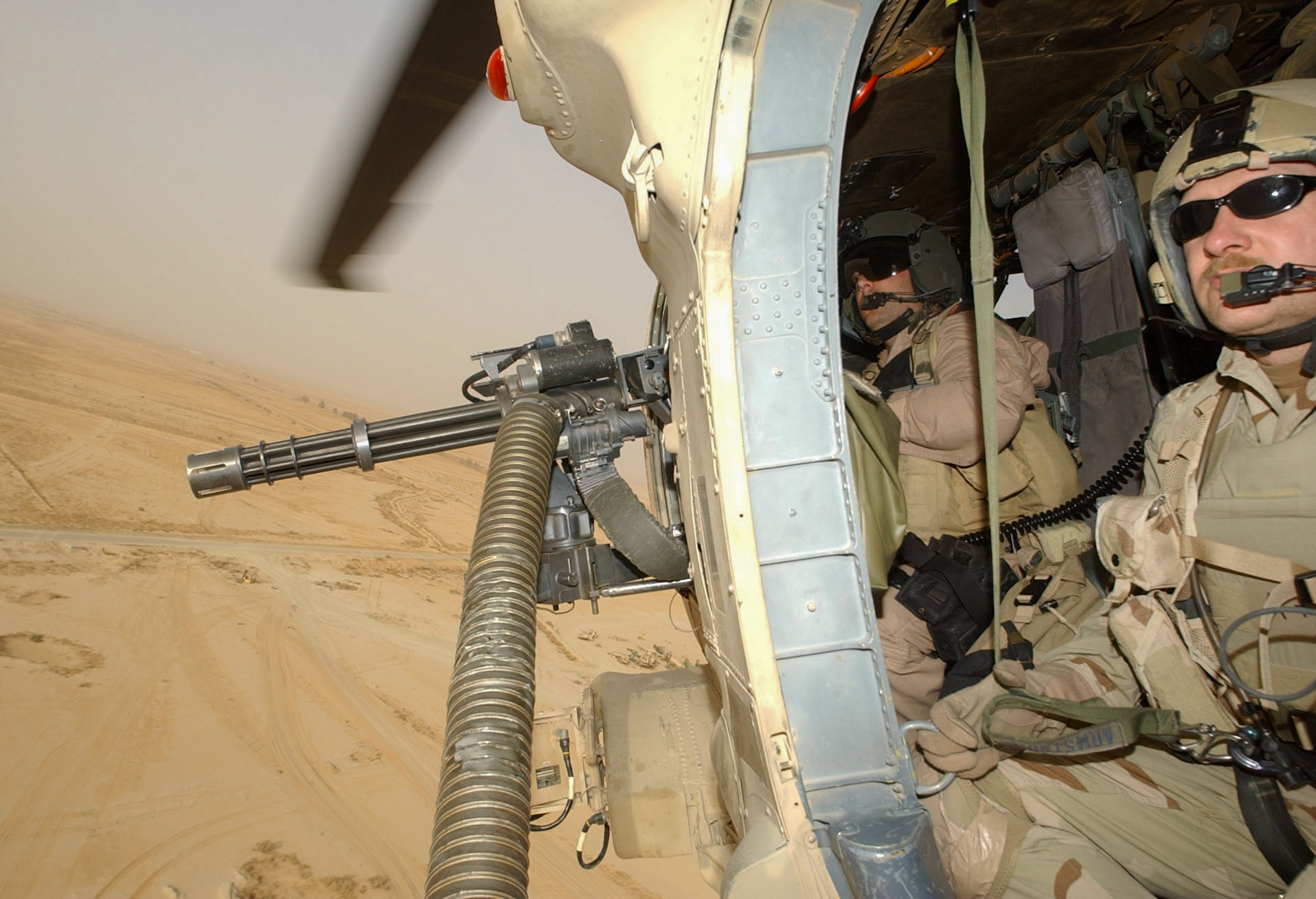 Staff Sgt.. Anthony Pieske, left, door gunner on HH-60 Pavehawk, mans gun next to pararescueman Master Sgt. David Armstrong, right, while flying a search and rescue flight over southern Iraq on Monday. (Alan Lessig/Air Force Times)