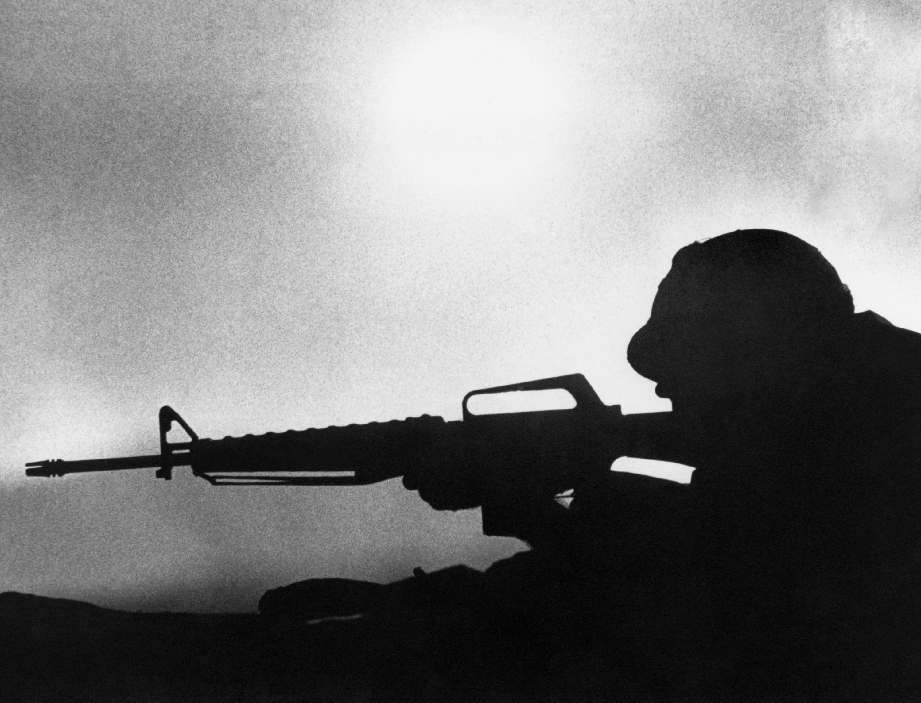 The setting sun silhouettes a U.S. Marine firing his rifle into suspected North Vietnamese positions at the encircled the Sanh Base, March 18, 1968. (AP Photo)