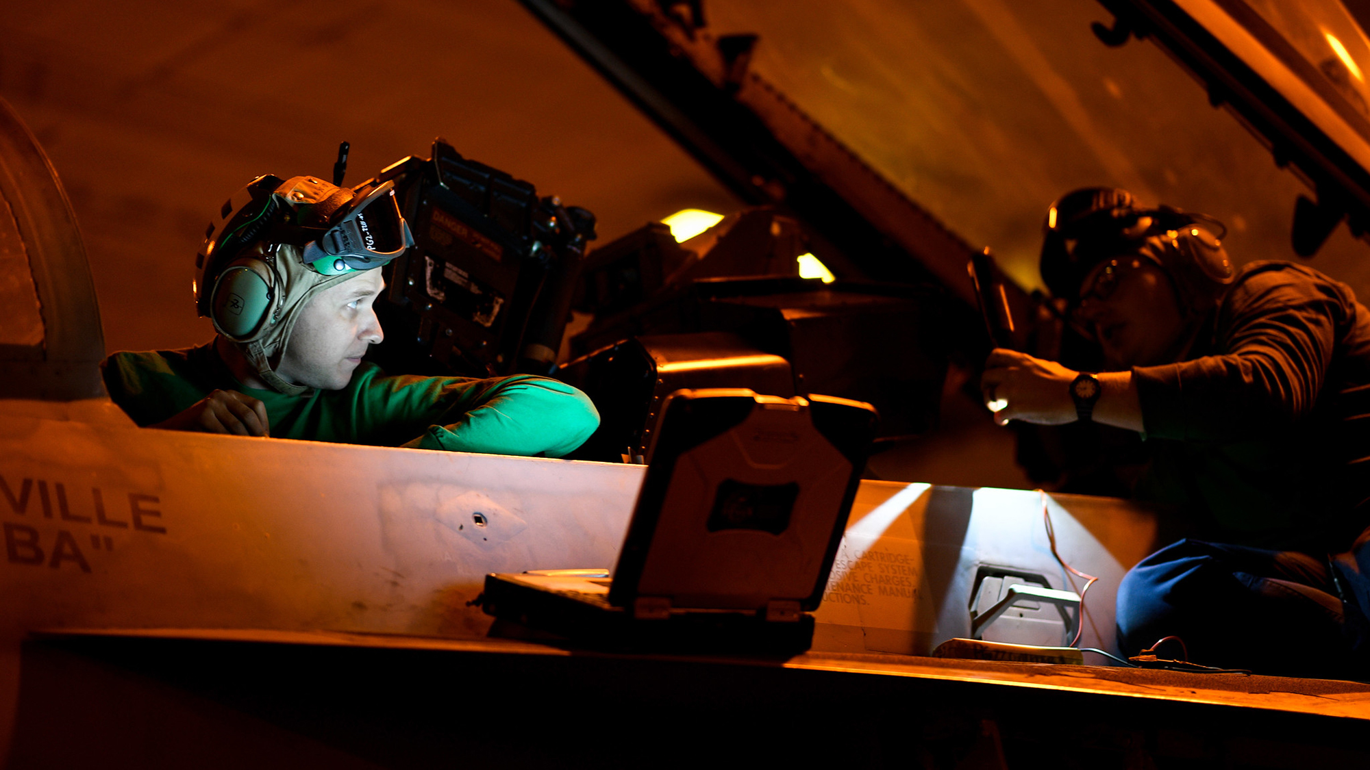 Aviation Electrician's Mate 2nd Class Trevor Brewster, left, and Aviation Electrician's Mate 3rd Class Caleb Byers run diagnostics on the weapons system of an F/A-18F Super Hornet on Nov. 20, 2019, in the hangar bay of the aircraft carrier USS Theodore Roosevelt (CVN 71) in the Pacific Ocean. (Mass Communication Specialist Seaman Olympia O. McCoy/Navy)