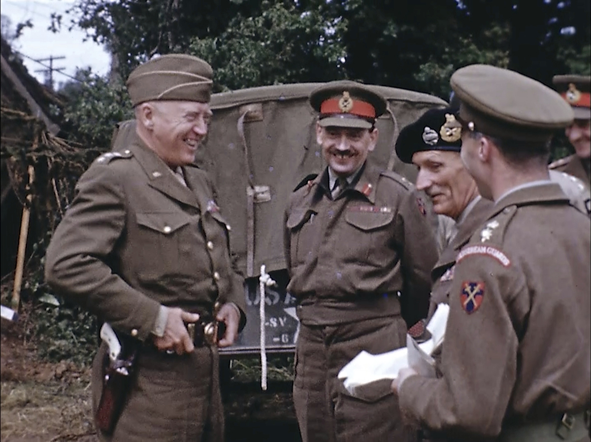 U.S. Army Gen. George Patton, left, with a pearl-handled pistol, talks to British Field Marshal Bernard Montgomery, center right with the beret hat, and other British officers in France during World War II. Seventy-five years later, surprising color images of the D-Day invasion and aftermath bring an immediacy to wartime memories. They were filmed by Hollywood director George Stevens and rediscovered years after his death. (War Footage From the George Stevens Collection at the Library of Congress via AP)