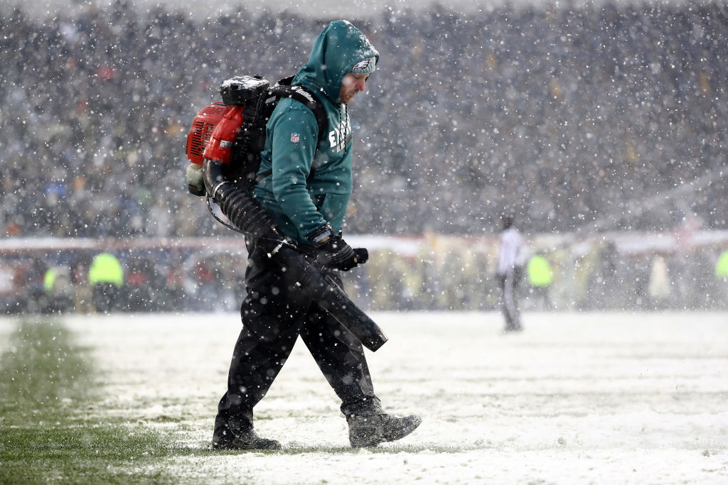 A grounds crew member uses a leaf blower to clear the field during Saturday's Army-Navy game in Philadelphia. (Elsa/Getty Images)