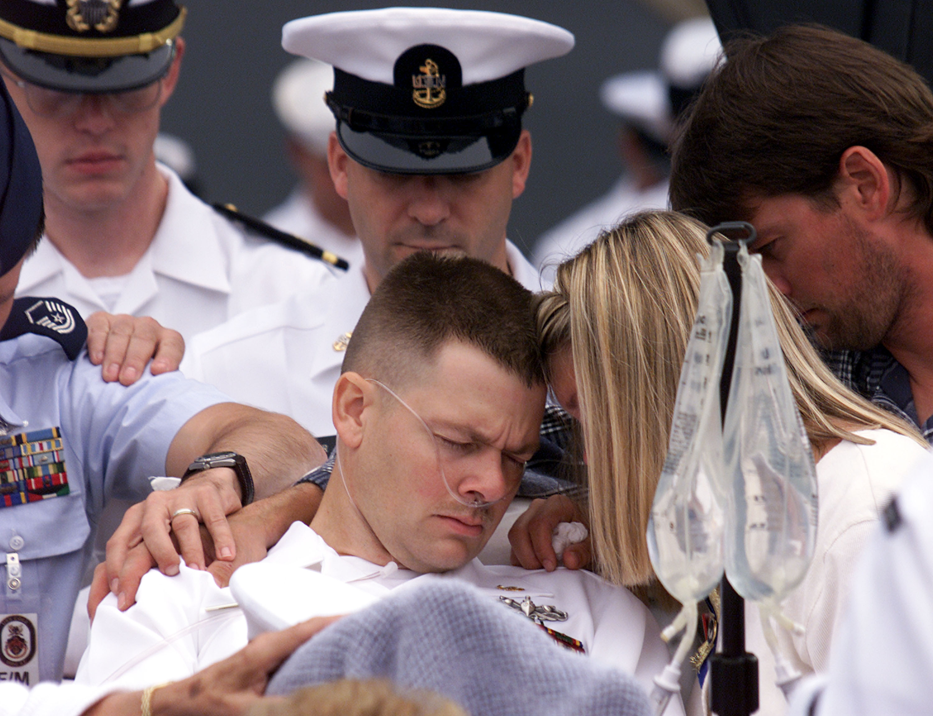 An injured sailor from the USS Cole is comforted by a family member during a memorial service October 18, 2000 in Norfolk VA. President Bill Clinton attended the service that honored the wounded and dead from the U.S. navy destroyer that was bombed while on a refueling stop in the Yemeni port of Aden. (Photo by Mark Wilson/Getty)