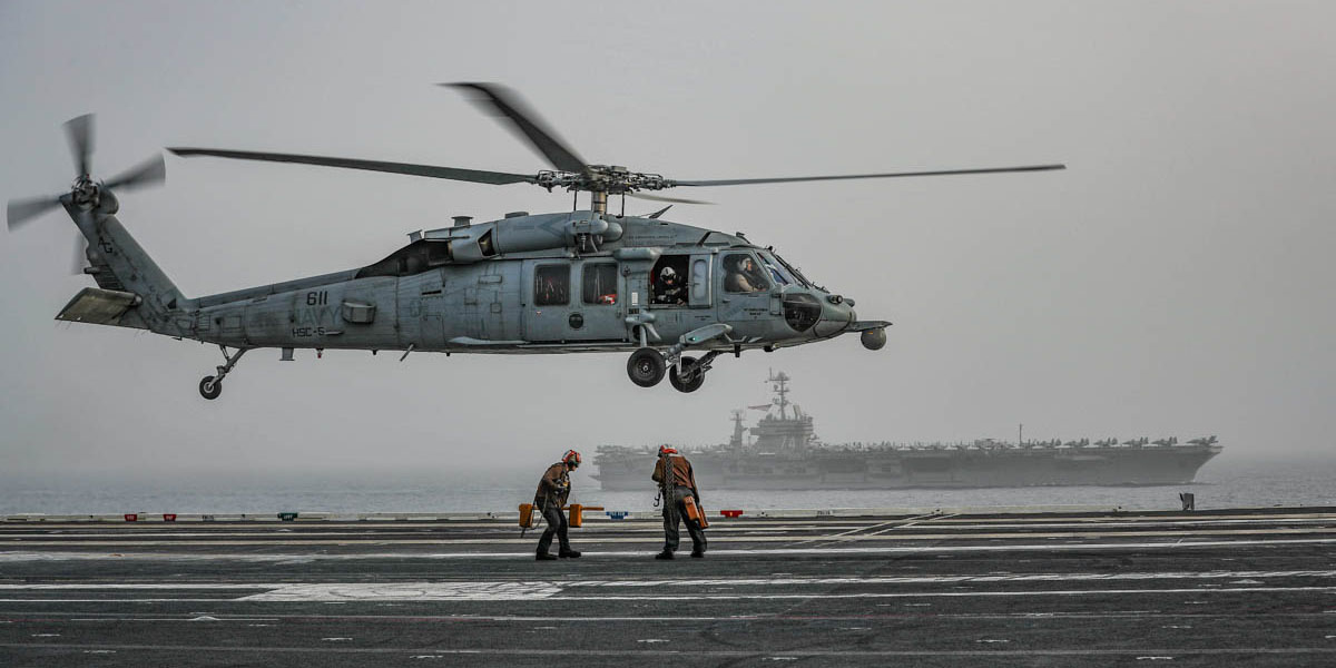 Flight deck plane captains prepare to secure an MH-60S Sea Hawk helicopter from the