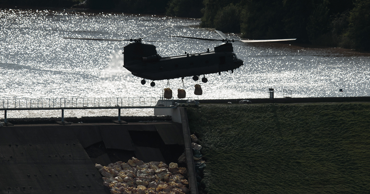 An RAF Chinook helicopter drops aggregate to help shore up a reservoir at risk of collapse, threatening to engulf the town of Whaley Bridge in the Peak District, England, Friday, Aug. 2, 2019. (AP Photo/Jon Super)