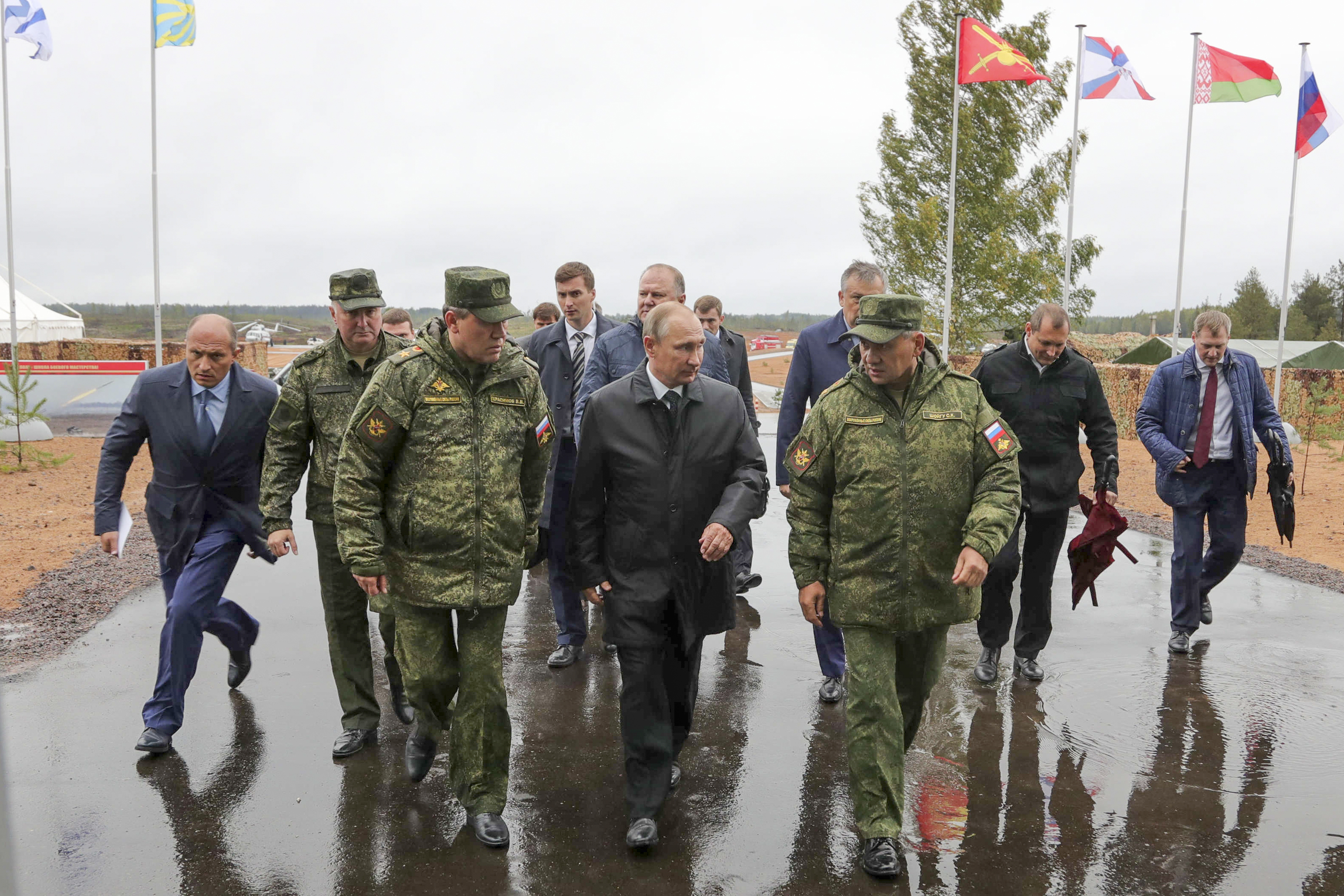 Russian President Vladimir Putin, center, walks with defense officials to attend a military exercise at a training ground at the Luzhsky Range, near St. Petersburg, Russia, on Sept. 18, 2017. (Sputnik/Kremlin Pool via AP)