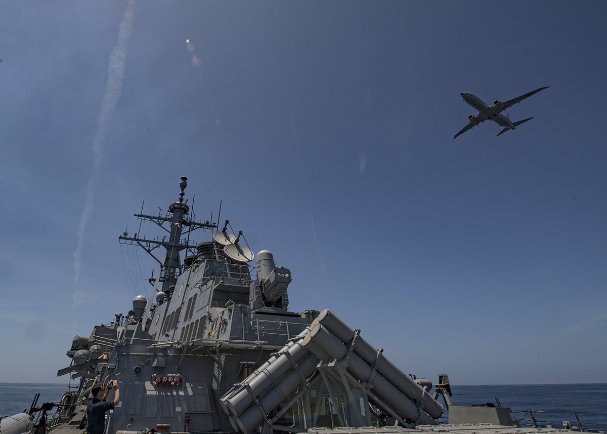 A P-8 Poseidon flies over the Arleigh Burke-class guided-missile destroyer USS Carney (DDG 64) during a air defense exercise, June 19, 2019, in the Atlantic Ocean. (Mass Communication Specialist 1st Class Fred Gray IV/Navy)