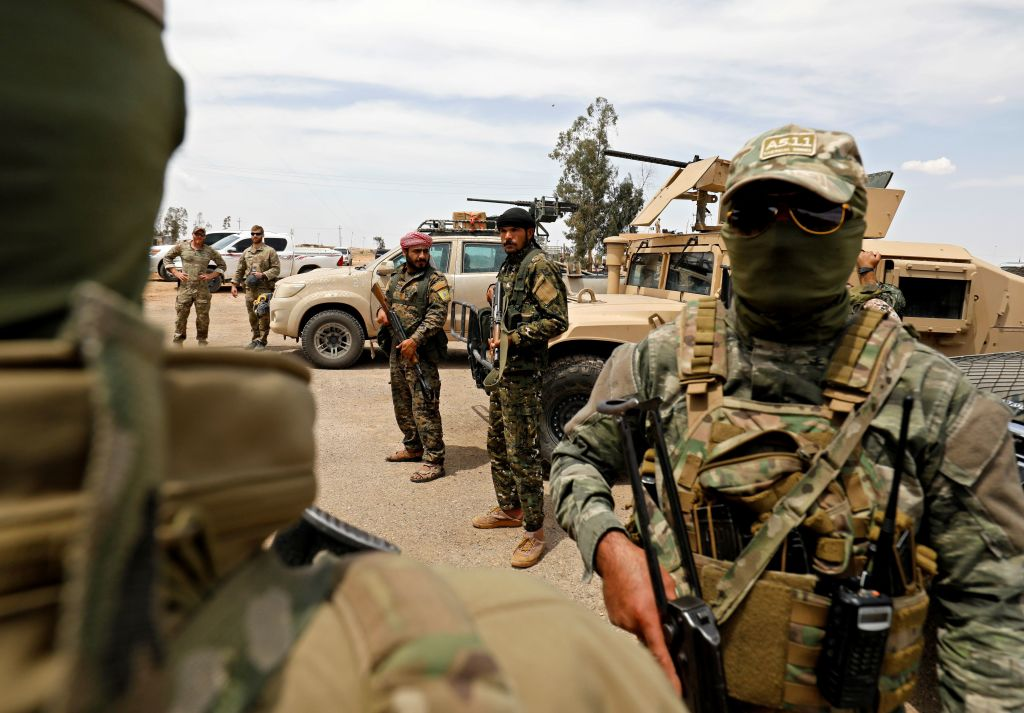 Members of the Syrian Democratic Forces and US soldiers, left, gather at the al-Tanak oil field as they prepare to relaunch a military campaign against the Islamic State group near Abu Kamal, province of Deir Ezzor, eastern Syria on May 1, 2018. (Delil Souleiman/AFP via Getty Images)