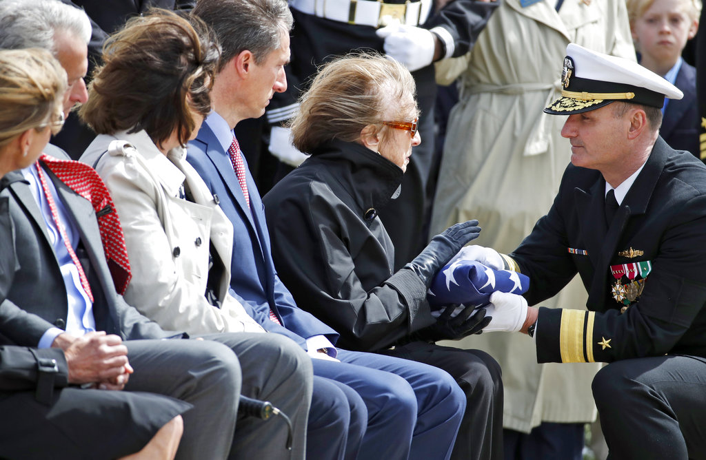 The flag is presented by U.S. Navy Rear Adm. William Galinis, right, to Georgea Hudner, during burial services for her husband, Capt. Thomas J. Hudner Jr., a naval aviator and Medal of Honor recipient from Concord, Mass., at Arlington National Cemetery Wednesday, April 4, 2018 in Arlington, Va. Hudner earned the Medal of Honor for his actions in the Battle of the Chosin Reservoir during the Korean War. (Alex Brandon/AP)