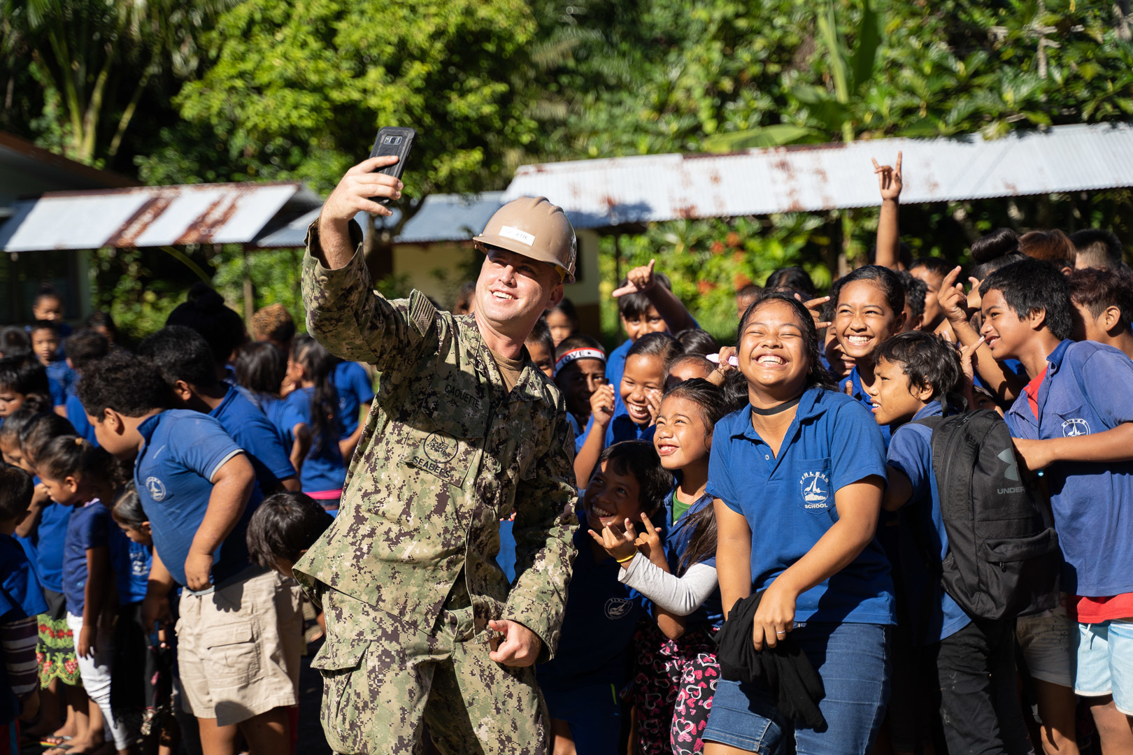 Equipment Operator Constructionman James Caouette takes a selfie with students from Pehleng Elementary School during the opening ceremony for the school's renovations on Nov. 7, 2019, in Pohnpei, Micronesia. (Builder 3rd Class Christian Carlson/Navy)