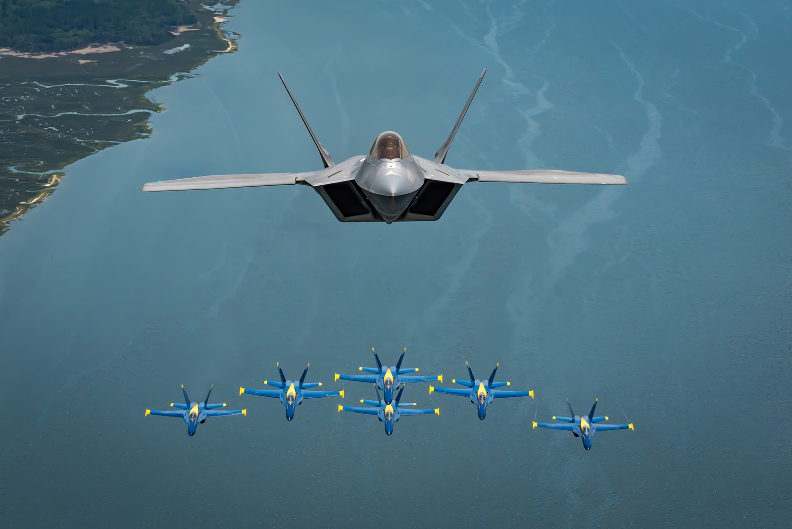 Maj. Paul Lopez, F-22 Demo Team commander, flies above the U.S. Navy Blue Angels' iconic diamond formation, over Beaufort, S.C., April 25, 2019. The historic flight featured two of the world's premier aerial demonstration teams side-by-side for the first time in history. (2nd Lt. Samuel Eckholm/Air Force)