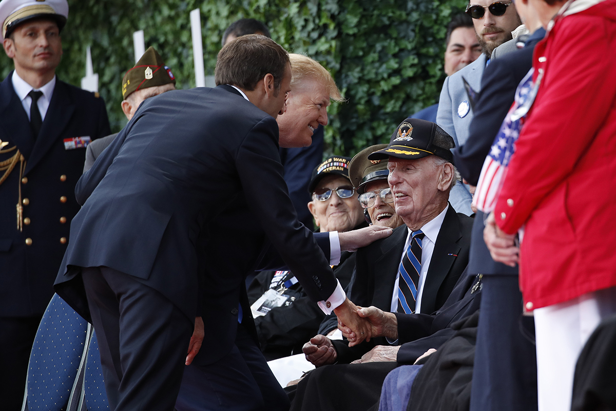 President Donald Trump and French President Emmanuel Macron greet veterans as they arrive to a ceremony to commemorate the 75th anniversary of D-Day at The Normandy American Cemetery, Thursday, June 6, 2019, in Colleville-sur-Mer, Normandy, France. (AP Photo/Alex Brandon)