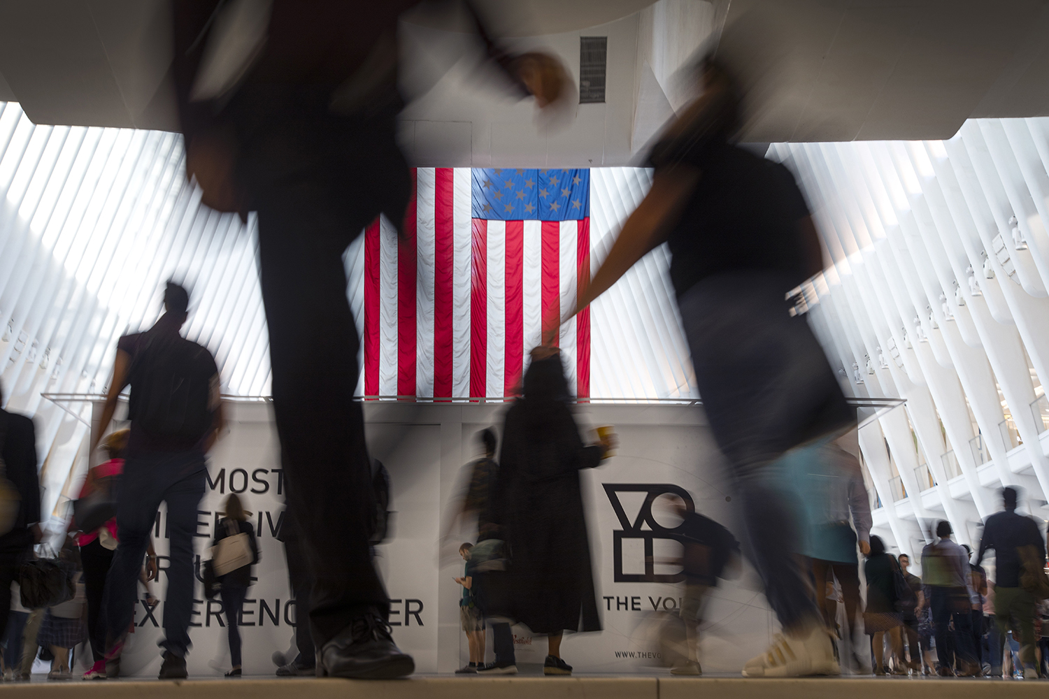 People walk past an American flag at the start of a work day, at the Oculus, part of the World Trade Center transportation hub in New York, Wednesday, Sept. 11, 2019, on the 18th anniversary of 9/11 terrorist attacks. (Wong Maye-E/AP)