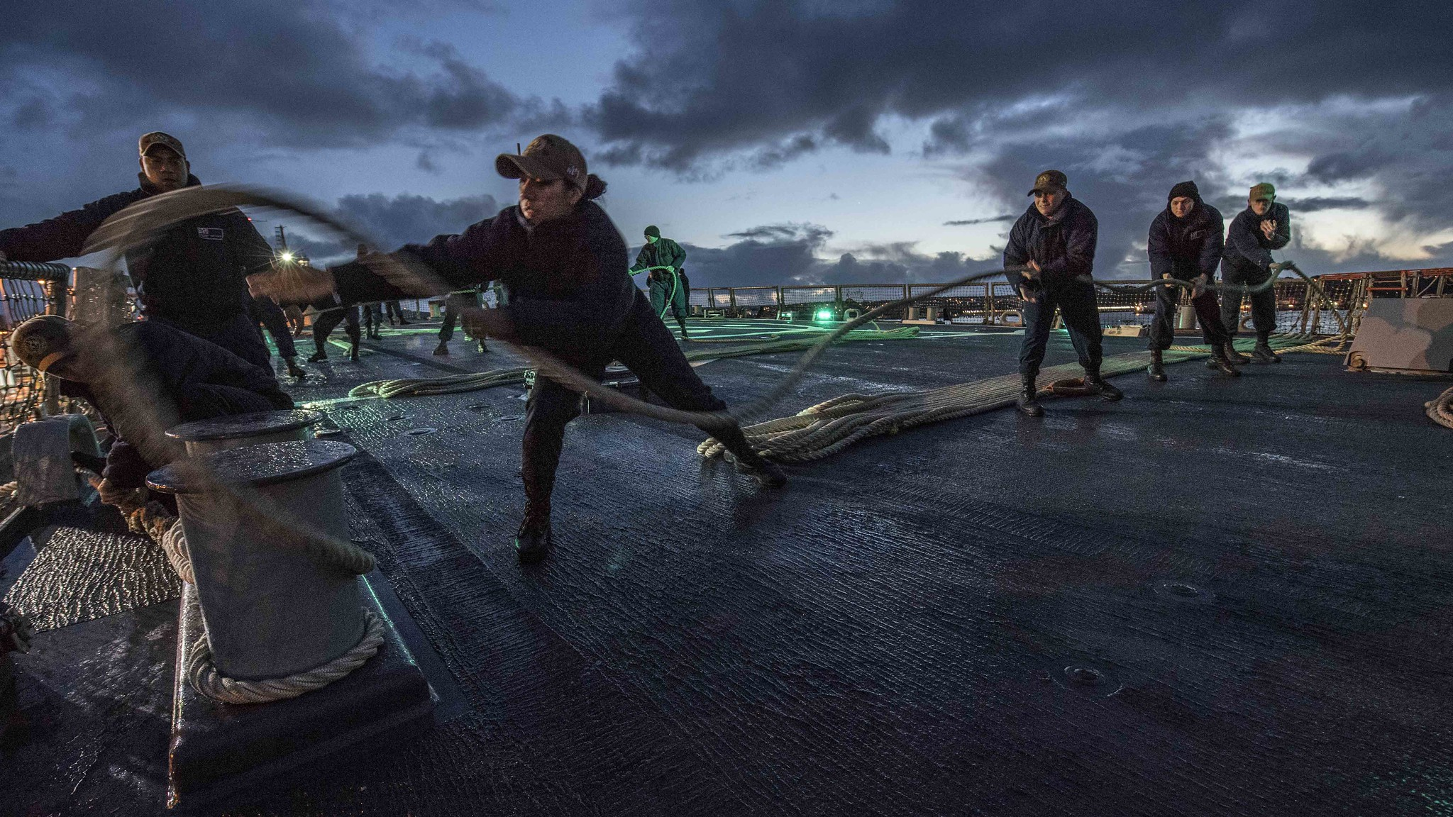 Sonar Technician (Surface) 2nd Class Vanessa Diaz, middle, throws a slacked mooring line around a set of bits during a sea and anchor evolution aboard the Arleigh Burke-class guided-missile destroyer USS Carney (DDG 64), Dec. 11, 2019, in Plymouth, England. (Mass Communication Specialist 1st Class Fred Gray IV/Navy)