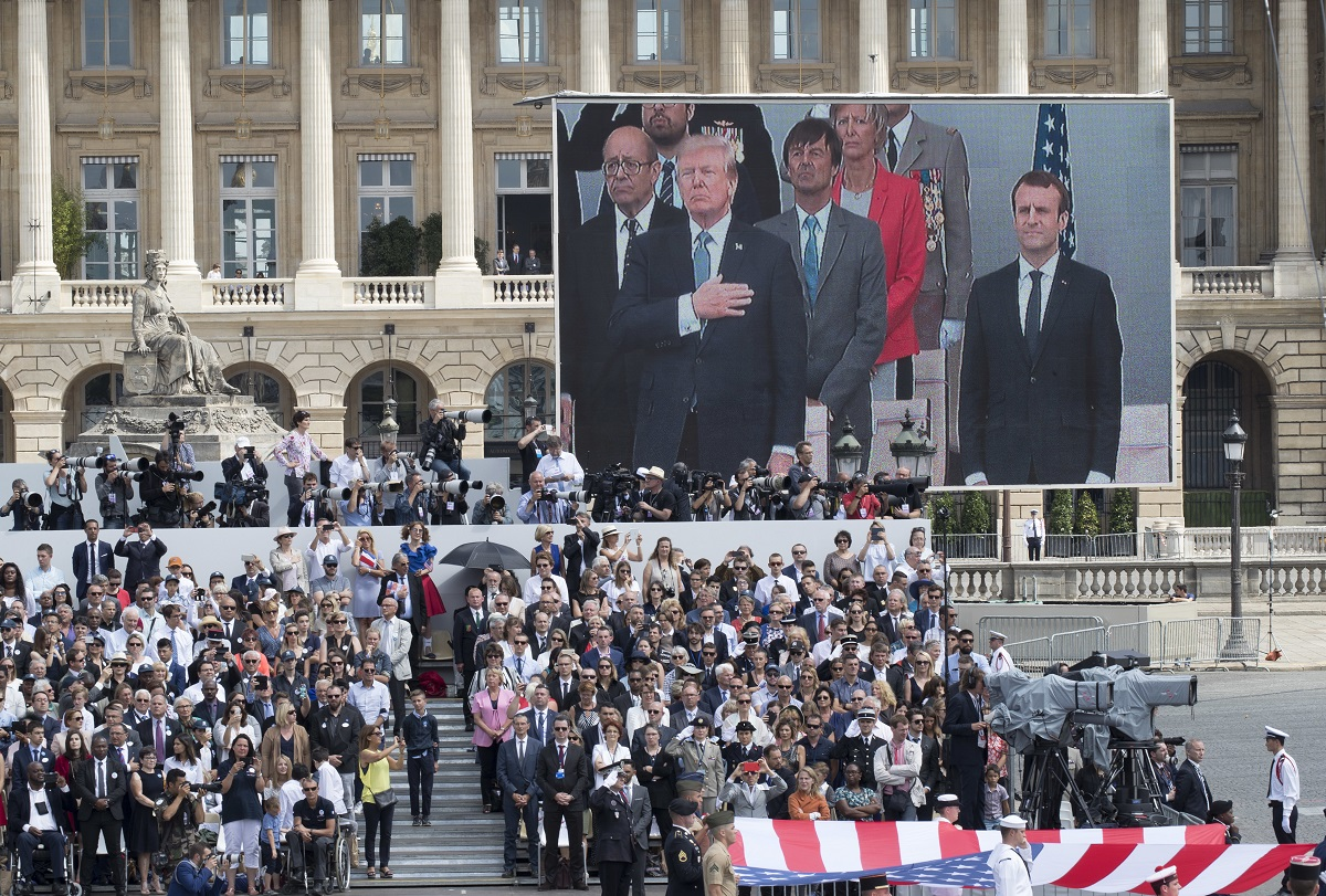 U.S. President Donald Trump and French President Emmanuel Macron are seen on a large screen as they stand during the American National Anthem during Bastille Day parade in Paris on July 14, 2017. The parade spurred Trump to request a similar celebration in the U.S. (Carolyn Kaster/AP)