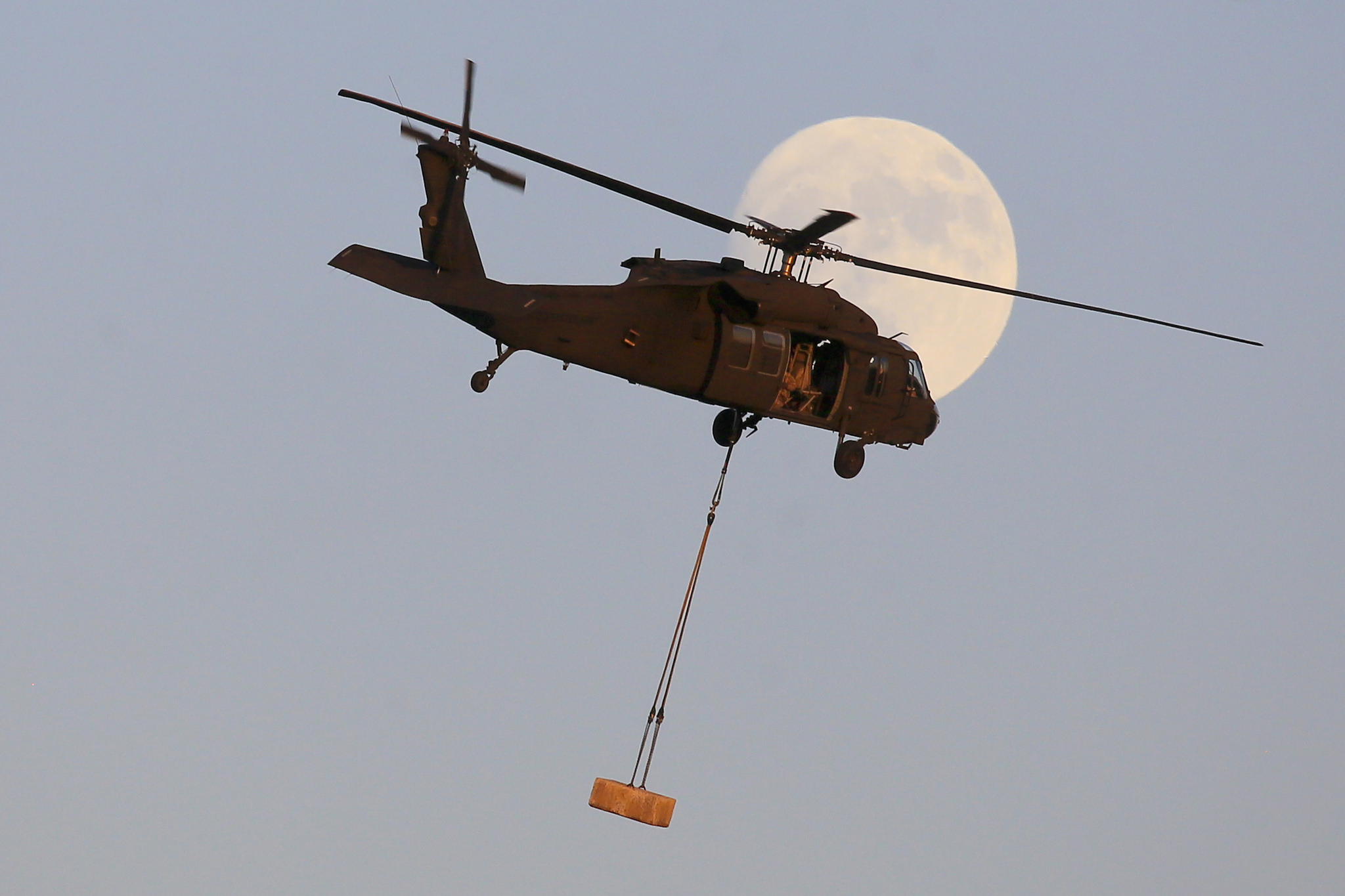 A New Jersey National Guard UH-60 Black Hawk from the 1-150 Assault Helicopter Battalion flies with a concrete block in front of the waxing gibbous moon during sling load training at Joint Base McGuire-Dix-Lakehurst, N.J., Dec. 1, 2017. (Master Sgt. Matt Hecht/Air National Guard)