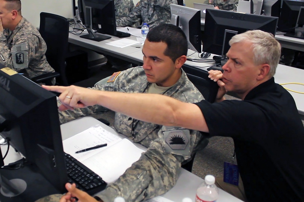Ken Foster, a computer network analyst with the California Army National Guard Computer Network Defense Team, assists one of his fellow analysts to defend against a simulated virus attack during the 2014 Cyber Shield exercise at the National Guard Professional Education Center in North Little Rock, Ark., April 30, 2014.