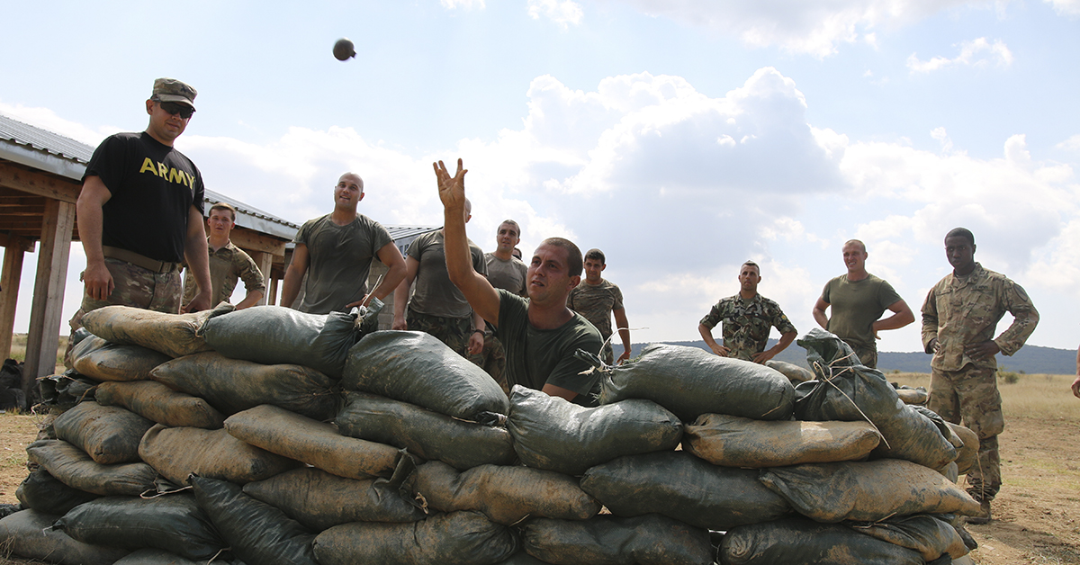 A Bulgarian Soldier assigned to 61st Mechanized Battalion, throws a training hand-grenade, during a team-building event of a spur ride, Novo Selo Training Area, Sept. 7, 2018. The spur ride is a time-honored cavalry tradition that gives cavalry troops the opportunity to earn silver spurs by participating in a series of physical and mental challenges, which helps create camaraderie and build esprit de corps. (Sgt. Jamar Marcel Pugh/Army National Guard)