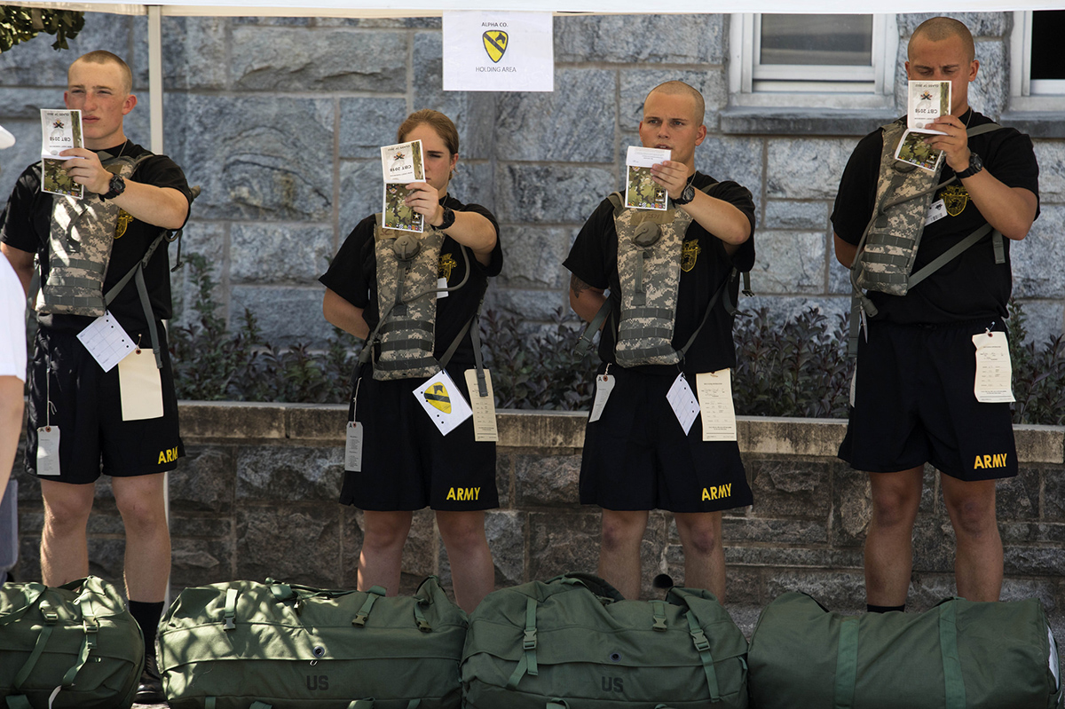 A new cadet reads the Cadet Basic Training book during Reception Day at the U.S. Military Academy at West Point July 2, 2018. During the six weeks of CBT, new cadets will be physically and mentally tested as they learn basic combat and leadership skills ahead of the academic year. (Michael Lopez/Army)