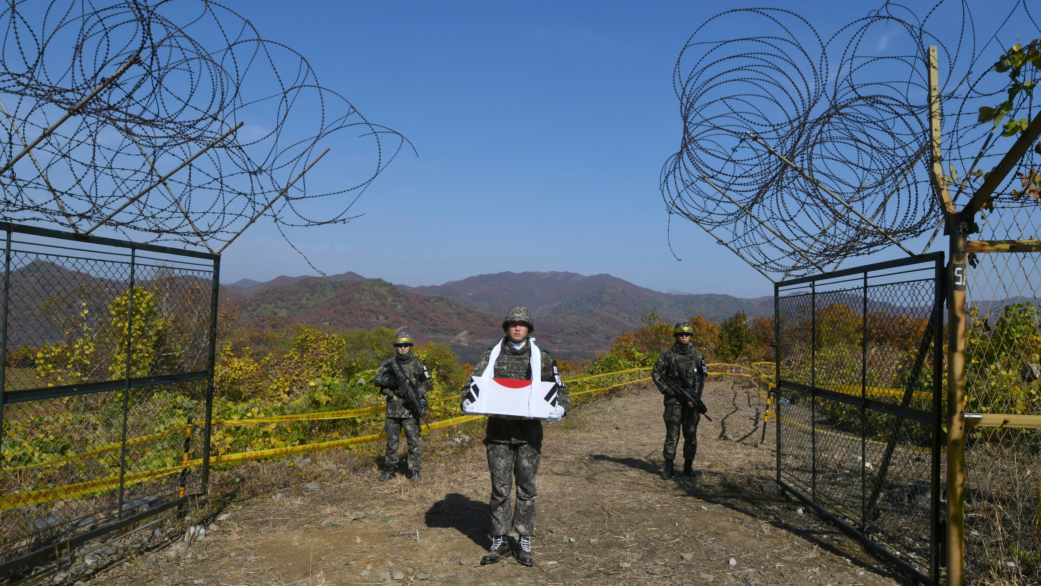 A South Korean soldier carries a coffin containing a piece of bone believed to be the remains of an unidentified South Korean soldier killed in the Korean War in the Demilitarized Zone (DMZ) dividing the two Koreas in Cheorwon, northeast of Seoul, Thursday, Oct. 25, 2018. The excavation project is part of a comprehensive military agreement that the two Koreas' defense ministers signed last month after the third summit between South Korean President Moon Jae-in and North Korean leader Kim Jong Un in Pyongyang. (Jung Yeon-je/Pool Photo via AP)