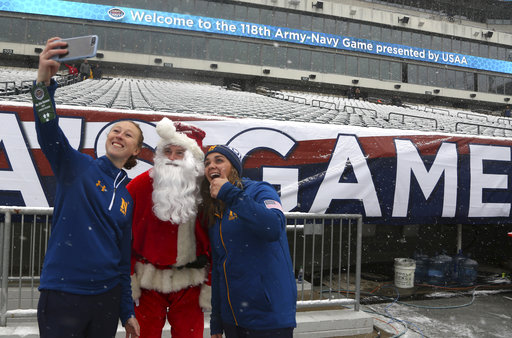 Navy athletic training personnel take a selfie with a security staffer dressed as Santa Claus before the 118th Army-Navy game Saturday in Philadelphia. (Jacqueline Larma/AP)