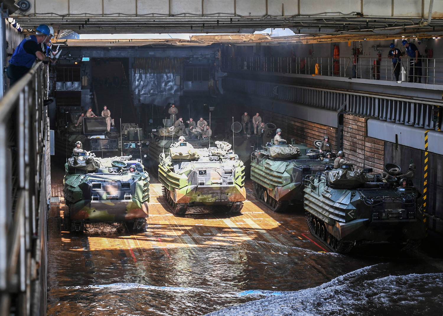 Sailors and Marines guide amphibious assault vehicles into the well deck aboard the Whidbey Island-class dock landing ship USS Germantown (LSD 42) on Oct. 4, 2019, in the Philippine Sea. (Mass Communication Specialist 1st Class Toni Burton/Navy)