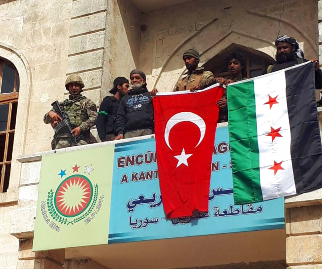 A Turkish and a Turkey-backed Free Syrian Army soldier wave Turkish and FSA flags in the city center of Afrin, northwestern Syria, early Sunday, March 18, 2018. Turkey's President Recep Tayyip Erdogan said Sunday that allied Syrian forces have taken