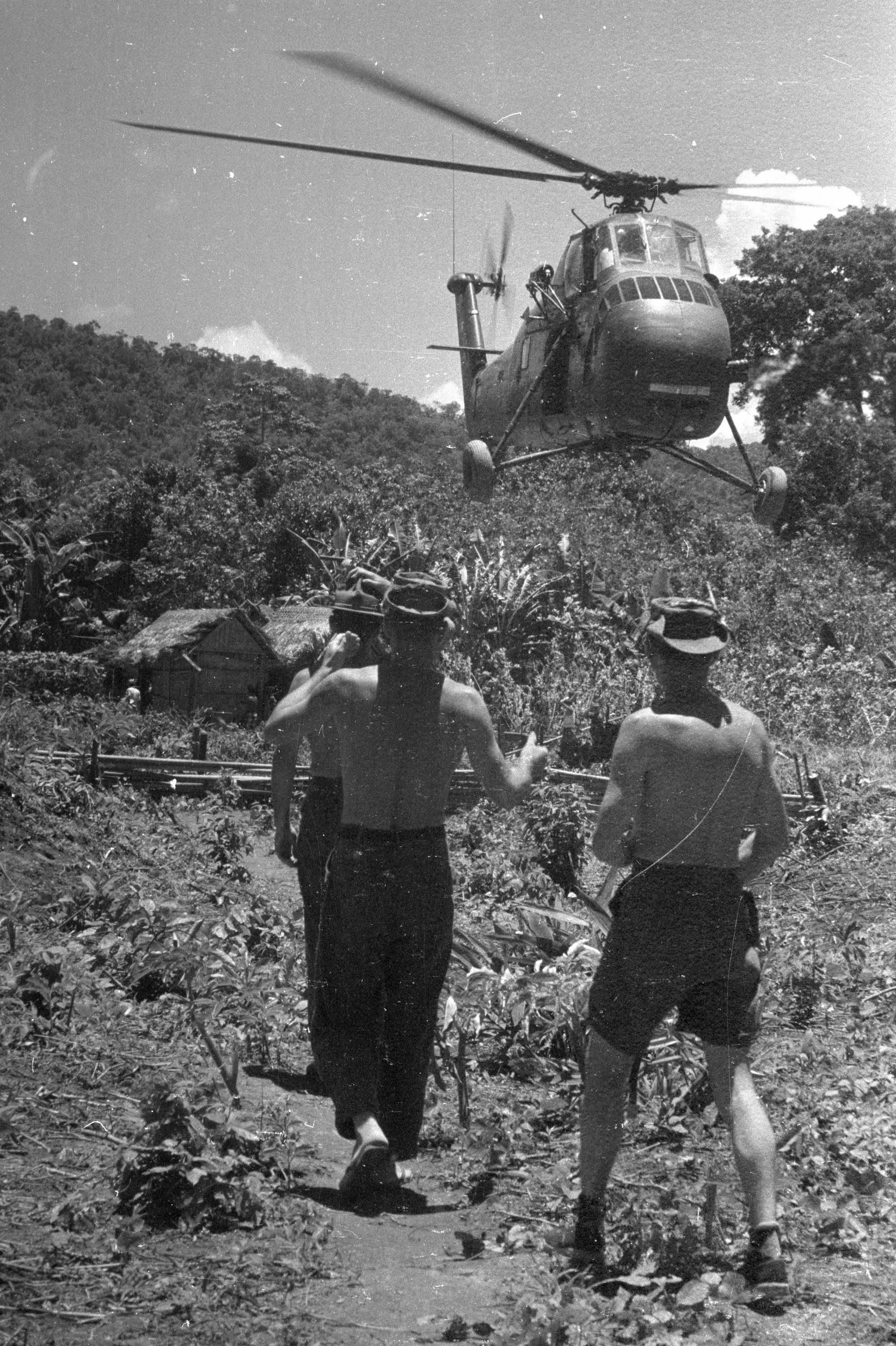 Soldiers watch an Air America helicopter land in Ban Hat Bay, Laos, 1961. (Wisconsin Historical Images 32770)