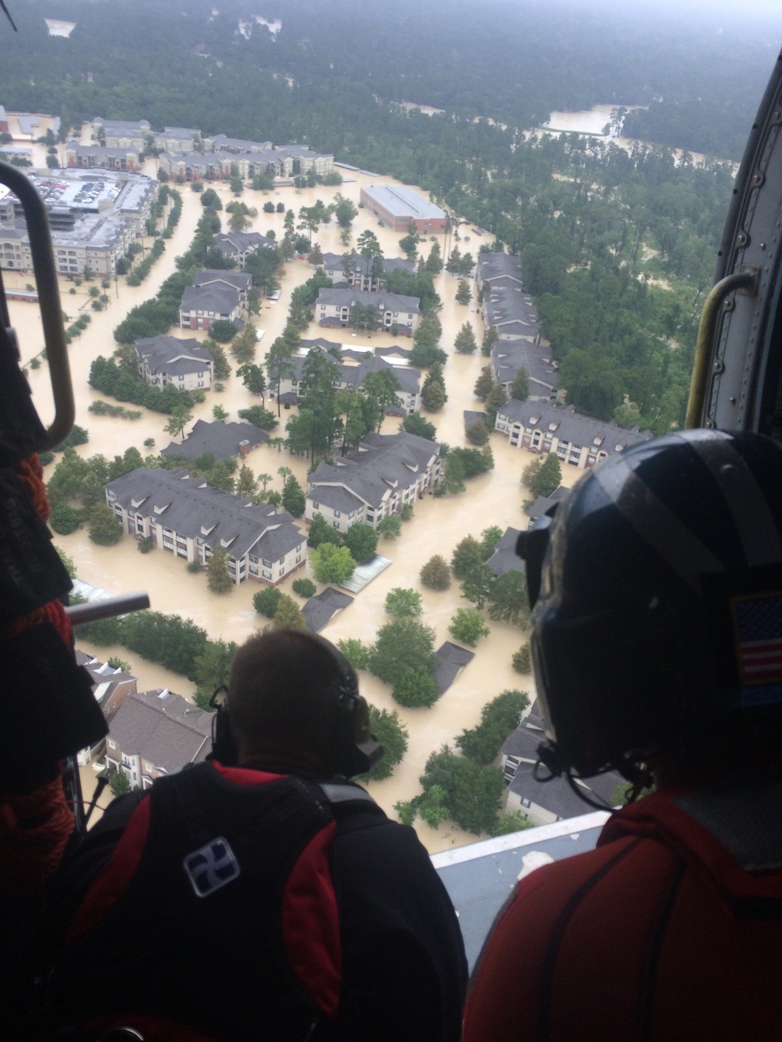 Members of the Kentucky Air National Guard's 123rd Special Tactics Squadron fly on board a U.S. Coast Guard helicopter near Houston, Texas, Aug. 29, 2017. The airmen are patrolling the area looking for people who are trapped in their homes or on rooftops. (Air National Guard photo)