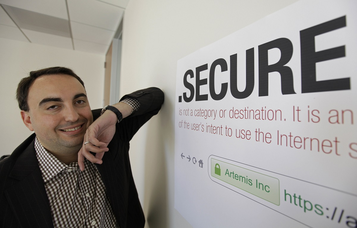In this photo taken Friday, June 8, 2012, Alex Stamos CTO of Artemis Internet, an NCC Group Company, poses by a domain name poster at their offices in San Francisco. Stamos served as chief security officer at Facebook for three years before joining Stanford University, where he studies internet security, including systems related to conducting elections. (Eric Risberg/AP)