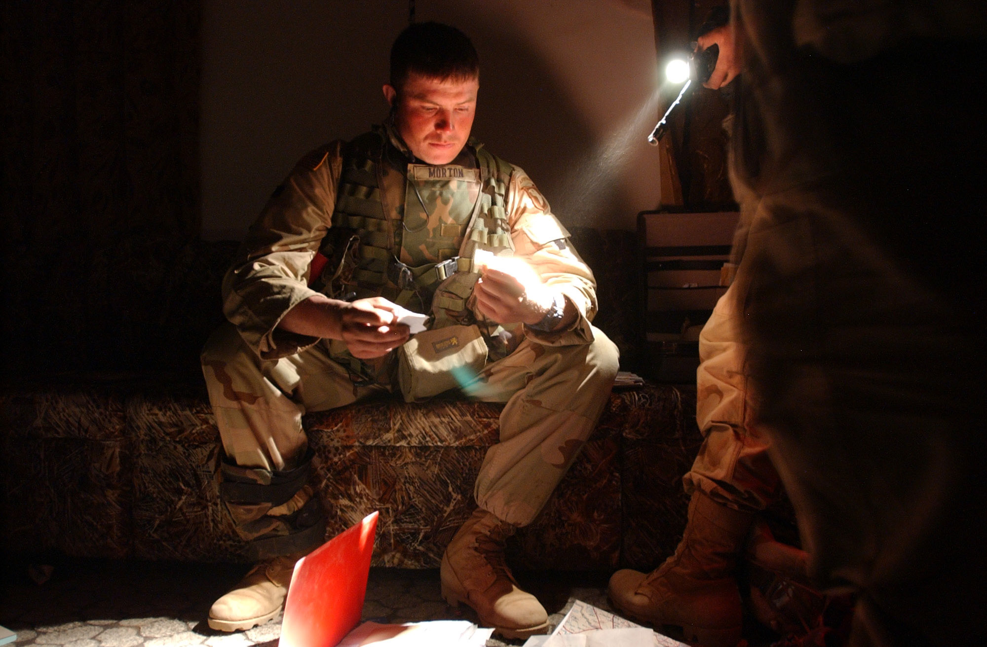 Staff Sgt. Todd Morton, 27, from Cohoes, NY, looks through documents and maps found after 2nd platoon, bravo company, 3rd Battalion, 2nd Brigade, 101st Airborne Divison (Air Assault) occupied a hastily abandoned residence during the Brigade's southern movement toward the city of An Najaf, Wednesday, 4/2/03. The infantry company searched several buildings turning up uniforms, communication equipment and gas masks, vehicles , dozens of small and large caliber weapons, RPGs, US style uniforms and other personal items, as well as uncovering at least two BM21, a Russian made Multiple Launch Rocket System (MLRS). (Rob Curtis/Army Times)