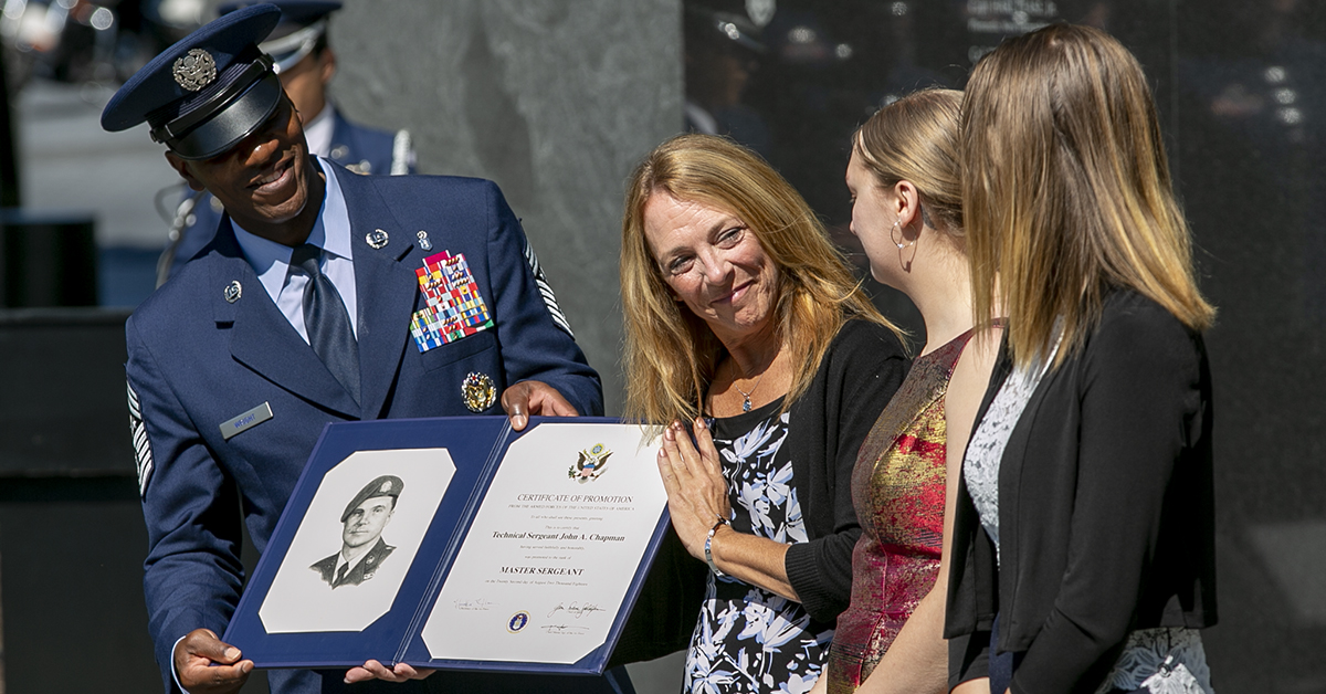 Chief Master Sgt. of the Air Force Kaleth O. Wright, left, presents Valerie Nessel, spouse of U.S. Air Force Tech. Sgt. John Chapman, and his daughters Brianna and Madison Chapman, with a letter of promotion raising his rank to Master Sgt. during a Medal of Honor unveiling ceremony at the Air Force Memorial. Chapman, was posthumously awarded the Medal of Honor on Wednesday for actions on Takur Ghar mountain in Afghanistan on March 4, 2002. (Alan Lessig/Staff)