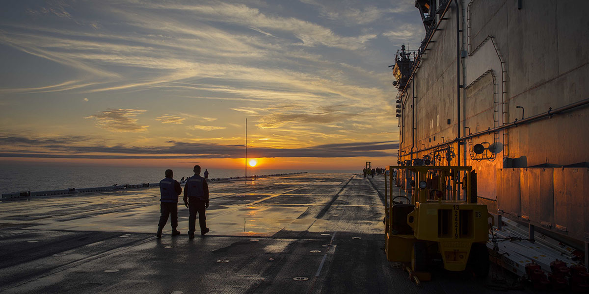 Sailors on the flight deck enjoy sunset aboard the amphibious assault ship Bataan while underway for sea trials. (Mass Communication Specialist 3rd Class Lenny Weston/Navy)