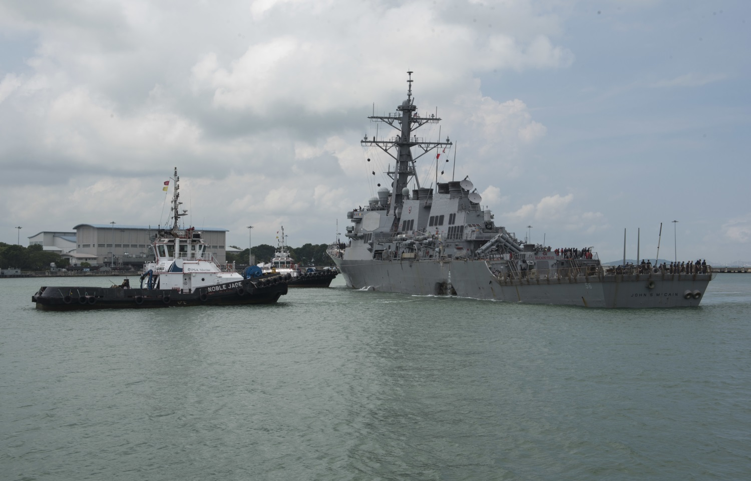 In this Aug. 21, 2017, photo provided by U.S. Navy, tugboats from Singapore assist the Guided-missile destroyer USS John S. McCain (DDG 56) as it steers towards Changi Naval Base, Singapore, following a collision with the merchant vessel Alnic MC while underway east of the Straits of Malacca and Singapore. (MC2 Joshua Fulton/Navy via AP)