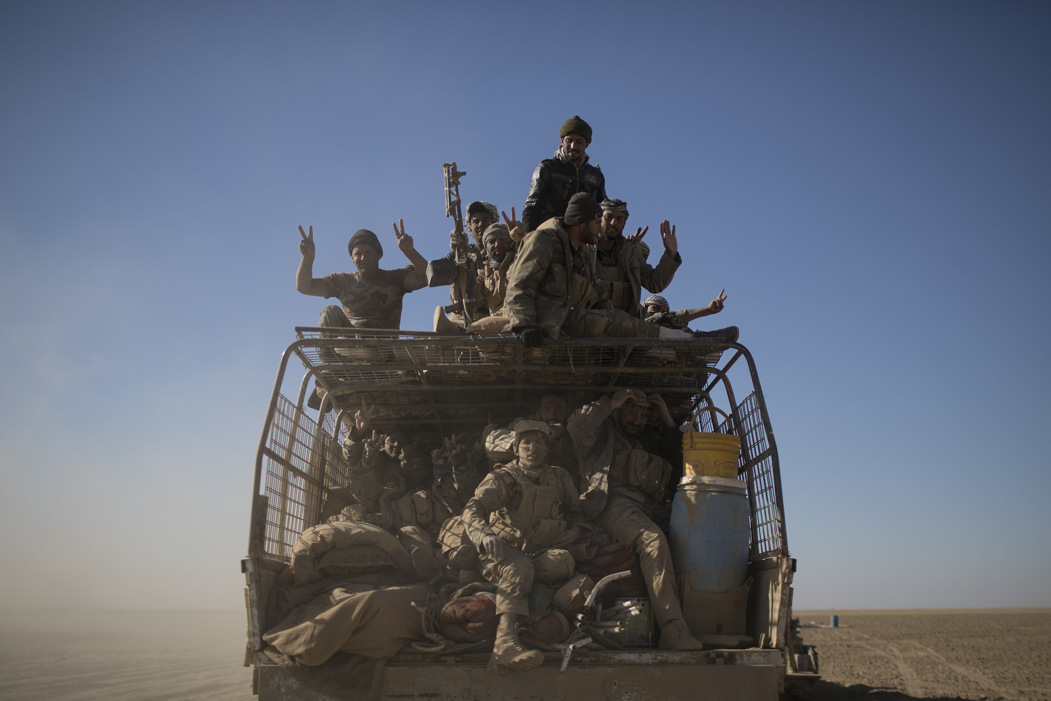 In this Nov. 20, 2016, file photo, Popular Mobilization Units fighters ride on the back of a truck on their way to fight against Islamic State militants in the airport of Tal Afar, west of Mosul, Iraq. (Felipe Dana/AP)