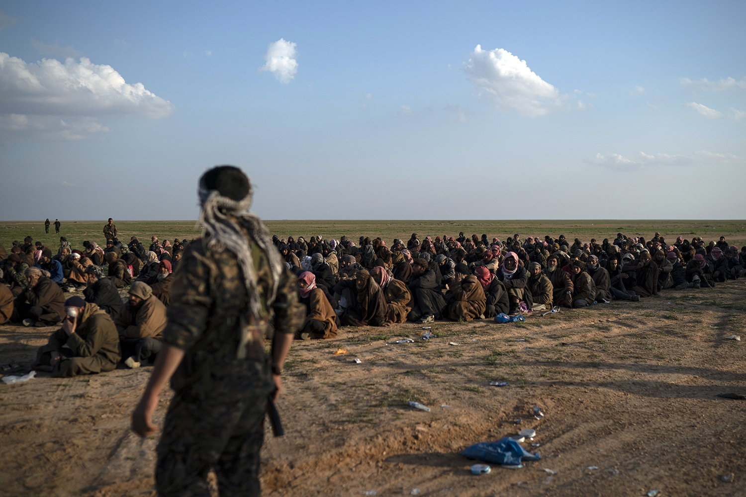In this Feb. 22, 2019, file photo, U.S.-backed Syrian Democratic Forces (SDF) fighters stand guard next to men waiting to be screened after being evacuated out of the last territory held by Islamic State group militants, near Baghouz, eastern Syria. (Felipe Dana/AP)