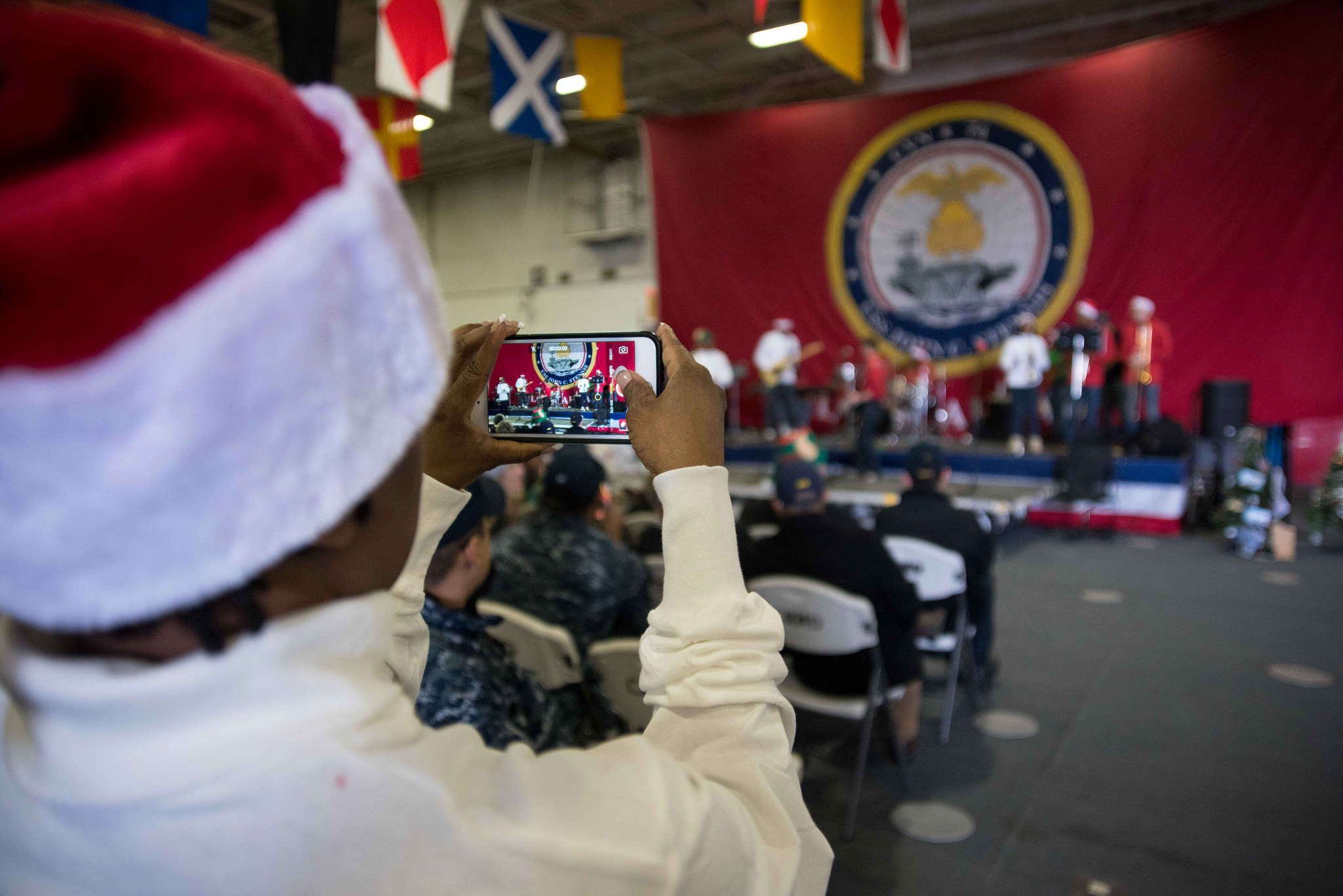 Sailors assigned to the aircraft carrier USS John C. Stennis (CVN 74) participate in a holiday event held by the ship's crew in the hangar bay on Dec. 15, 2017, in Bremerton, Wash. (MC3 William Ford/Navy)