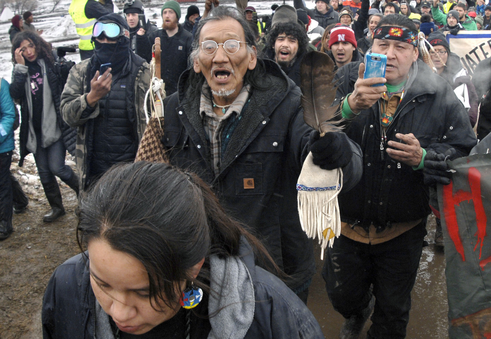 In this Feb. 22, 2017, file photo, a large crowd representing a majority of the remaining Dakota Access Pipeline protesters, including Nathan Phillips, center with glasses, march out of the Oceti Sakowin camp before the deadline set for evacuation of the camp near Cannon Ball, N.D. Phillips says he felt compelled to get between a group of black religious activists and largely white students with his ceremonial drum to defuse a potentially dangerous situation at a rally in Washington. (Mike McCleary/The Bismarck Tribune via AP)