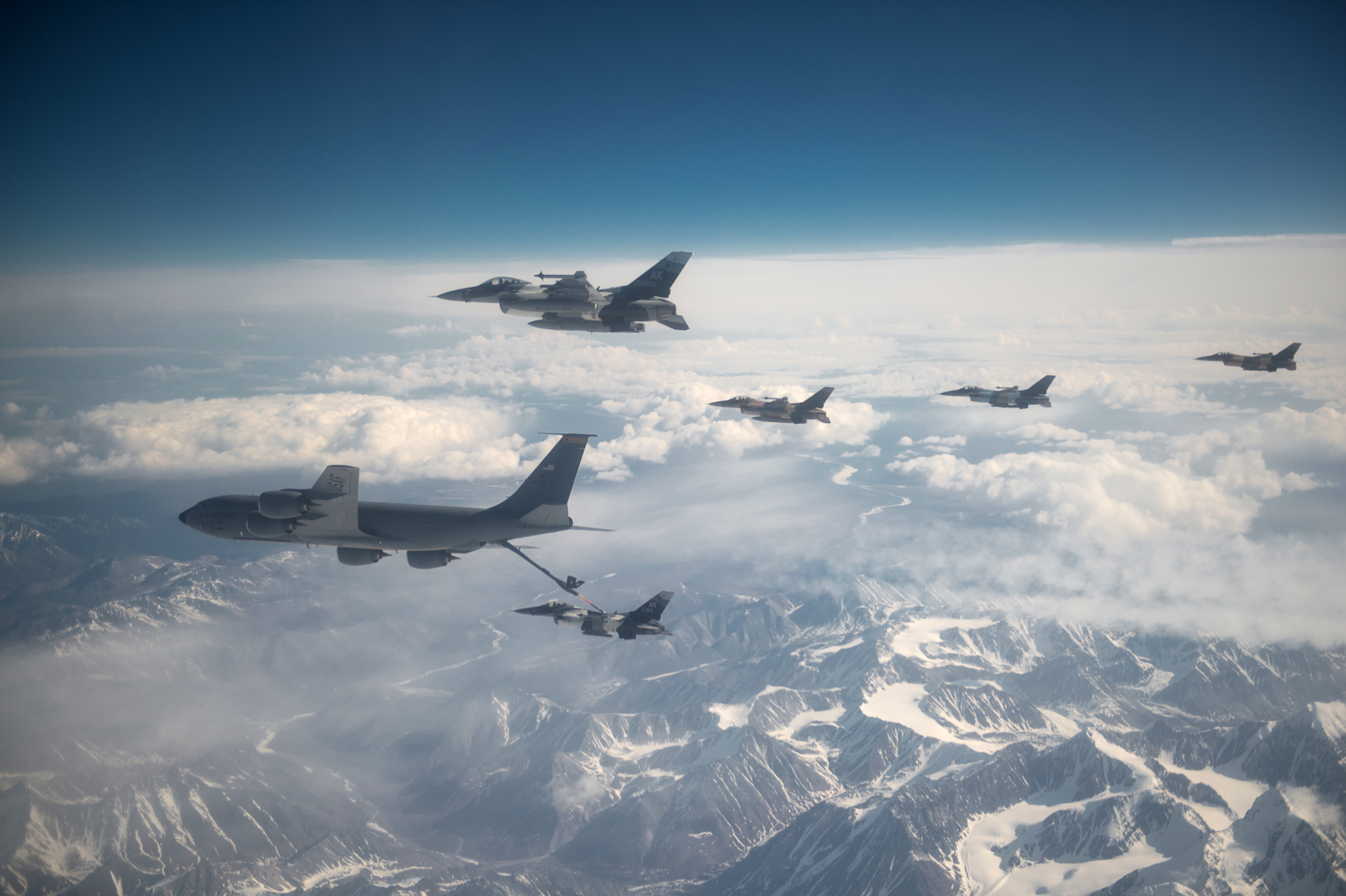 Air Force F-16 Fighting Falcons refuel behind a KC-135 Stratotanker during training operations in Alaska. (Staff Sgt. Shawn Nickel/Air Force)