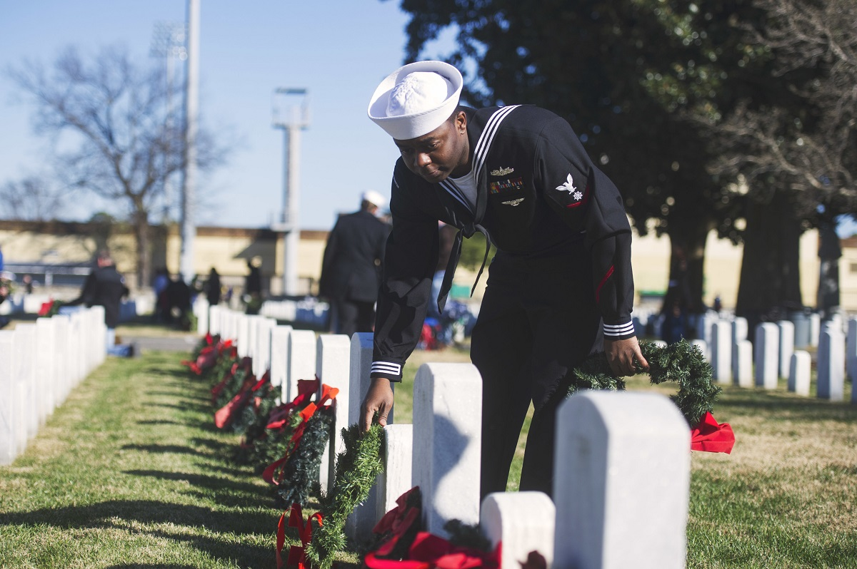 Quartermaster 3rd Class Moise Monestime, assigned to the Nimitz-Class aircraft carrier USS George Washington (CVN 73), lays a wreath on a grave during a Wreaths Across America ceremony Dec. 16, 2017, at Hampton National Cemetery in Virginia. (MC2 Jessica Gomez/Navy)