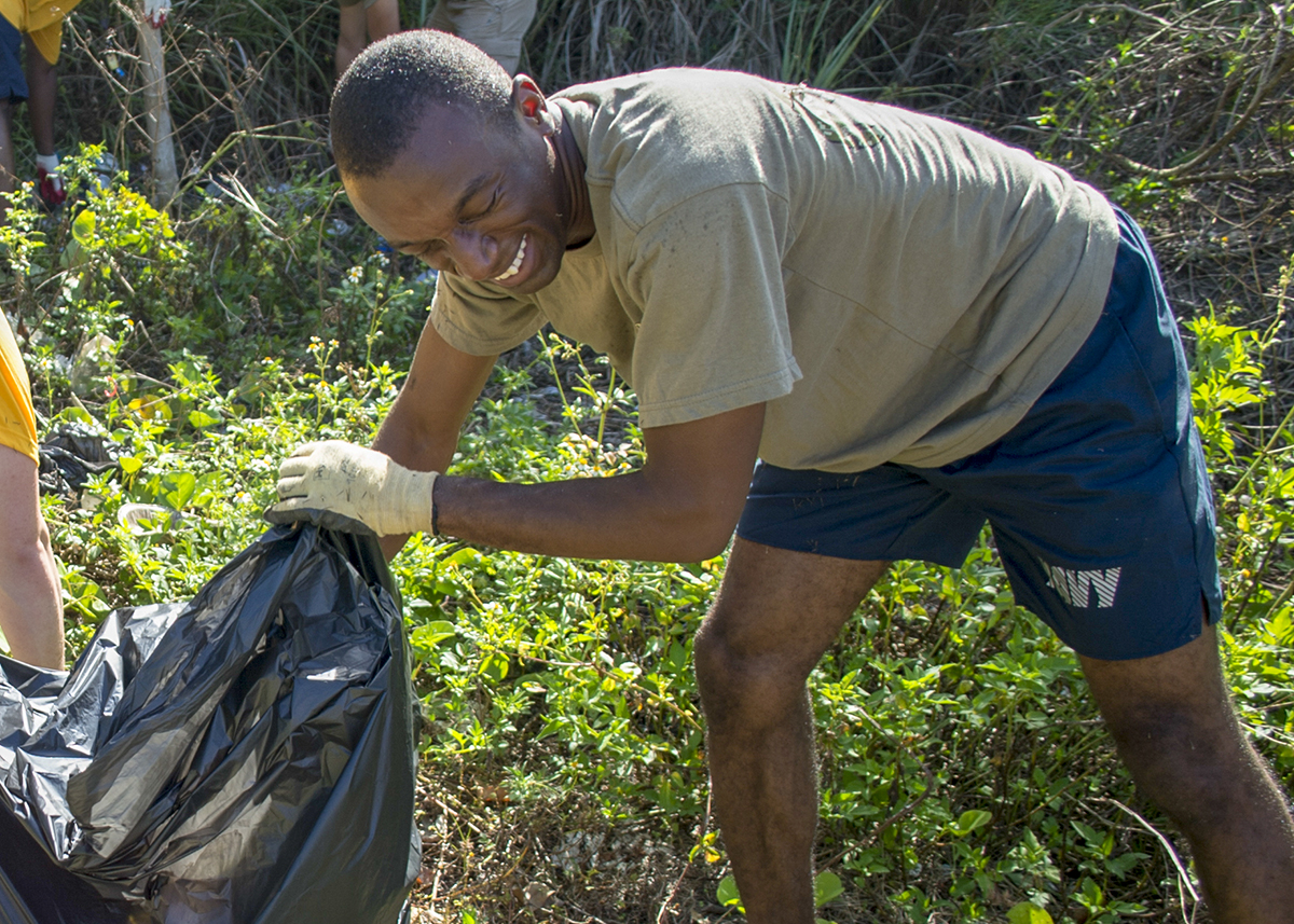 Electronics Technician Communications 1st Class Alex Hepburn, assigned to Submarine Squadron (SUBRON) 15, picks up trash behind the cemetery in Agat, Guam, April 20. More than 20 volunteers from SUBRON 15 and Performance Monitoring Team detachment Guam teamed up to pick up more than 40 bags of trash and other debris in Agat as part of an Earth Day clean-up. (Lt. Lauren Spaziano/Navy)