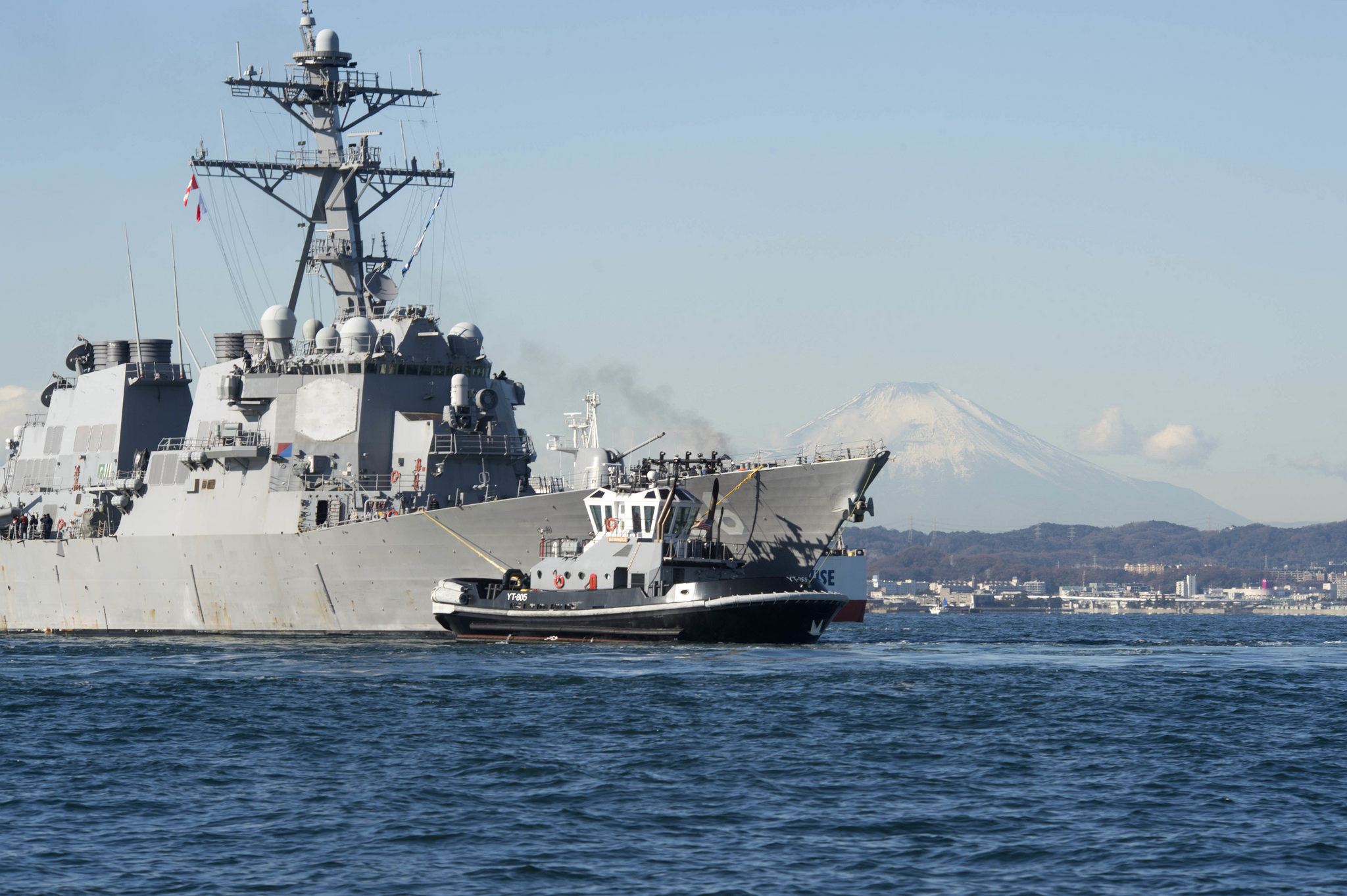 The Arleigh Burke-class guided-missile destroyer USS John S. McCain (DDG 56) is towed to the pier at Fleet Activities Yokosuka on Dec. 13, 2017. John S. McCain will undergo repairs at Ship Repair Facility – Japan Regional Maintenance Center in Yokosuka. (MC2 William McCann/Navy)