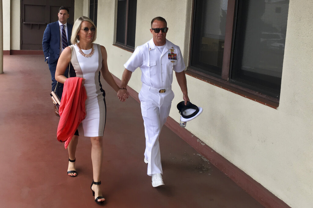 """Special Warfare Operator Chief Edward """"Eddie"""" Gallagher, right, walks with his wife, Andrea, as they arrive for court on Naval Base San Diego on Tuesday, (Julie Watson/AP)"""