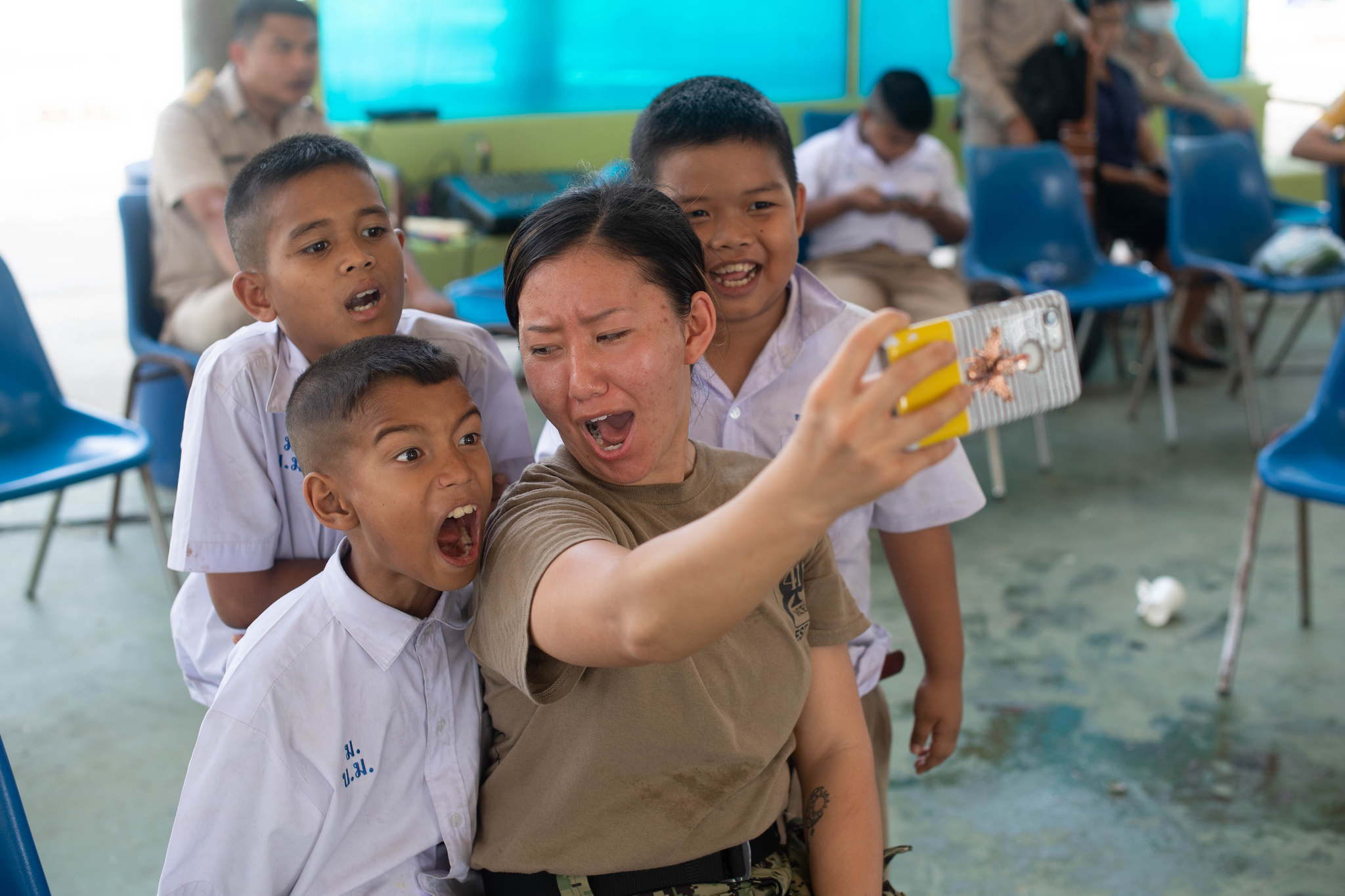 Navy Aviation Machinist's Mate 2nd Class Txi Txi Mee Lee, from Oshkosh, Wis., poses for a selfie with children Feb. 11, 2019, during a community outreach event at the Ban Banglamung School in in Laem Chabang, Thailand. Sailors assigned to the John C. Stennis Carrier Strike Group volunteered at the Ban Banglamung School during a scheduled port visit to Laem Chabang. (Mass Communication Specialist 3rd Class Grant G. Grady/Navy)
